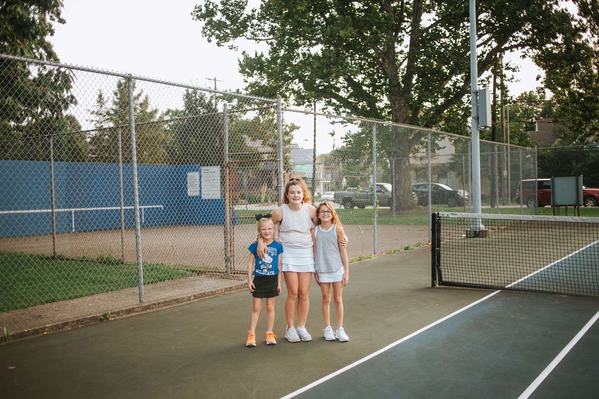 The Buffano sisters stand next to each other on a tennis court. Isabella, the oldest, has her arms around her younger sisters. All are smiling.
