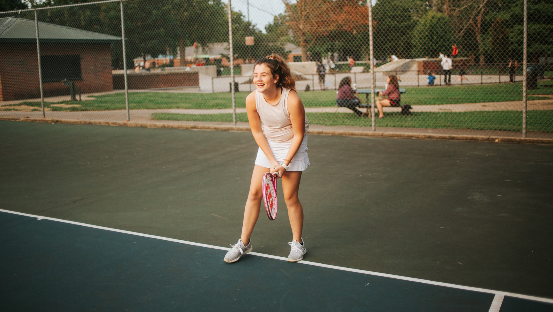 An action shot of Isabella, 12 years old, on the tennis court. She is wearing a white skirt and a gray tank top, and her curly brown hair is pulled back inn a ponytail.