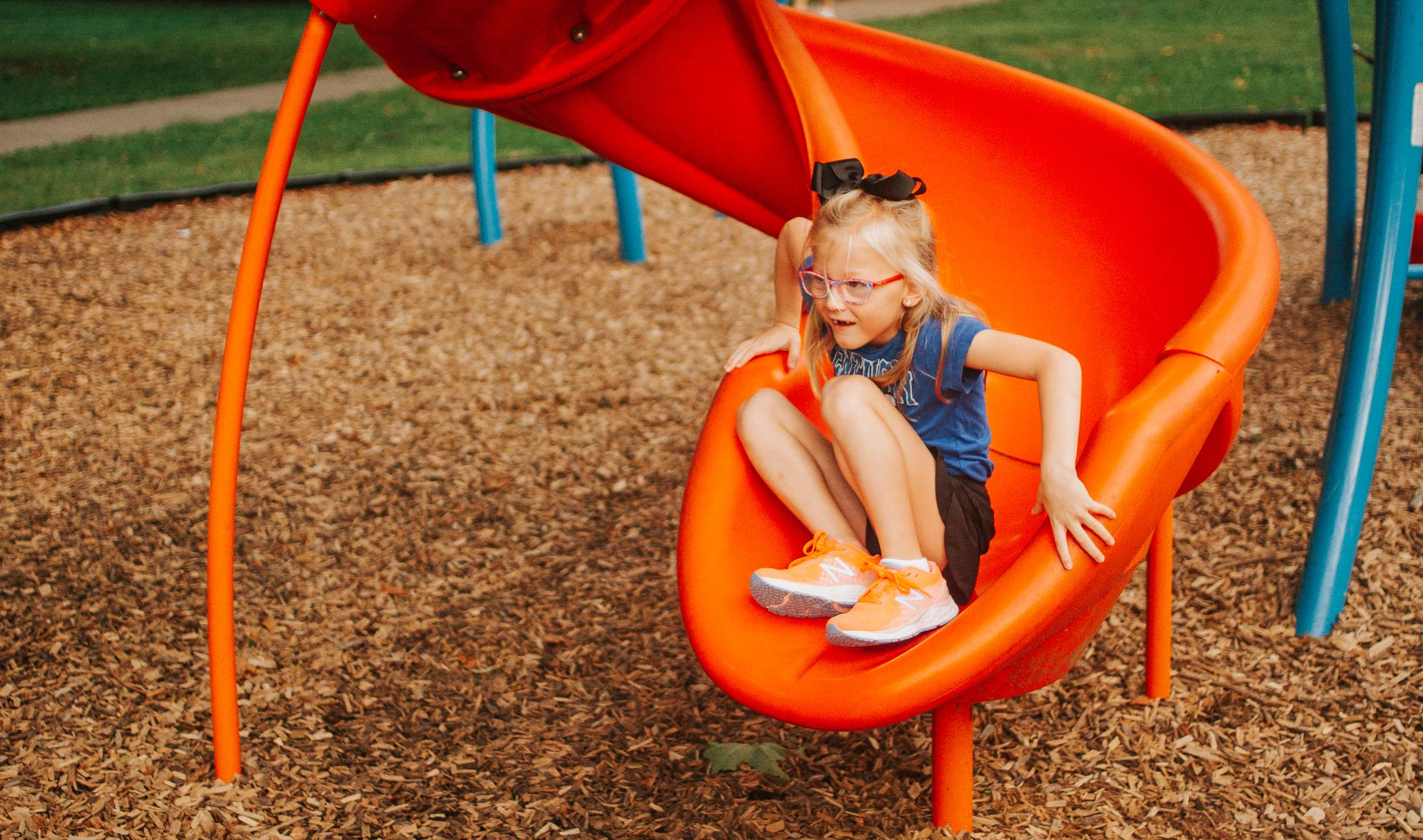 Olivia Buffano, six years old, comes down a slide. She has blonde hair with a black bow in it, and is wearing a blue Kentucky shirt, orange sneakers, a black skirt, and pink glasses.