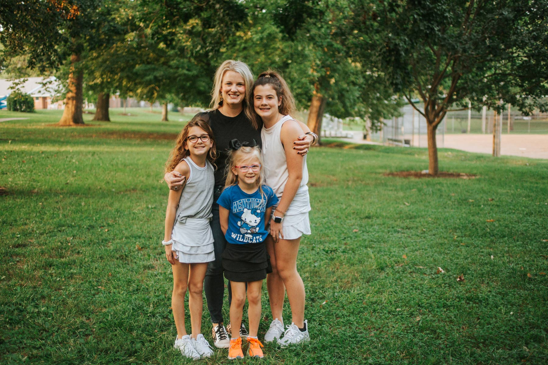 Kelley Buffano, a middle-aged white woman with blonde hair, stands in a park hugging her three daughters: Gabriellla, Olivia, and Isabella.