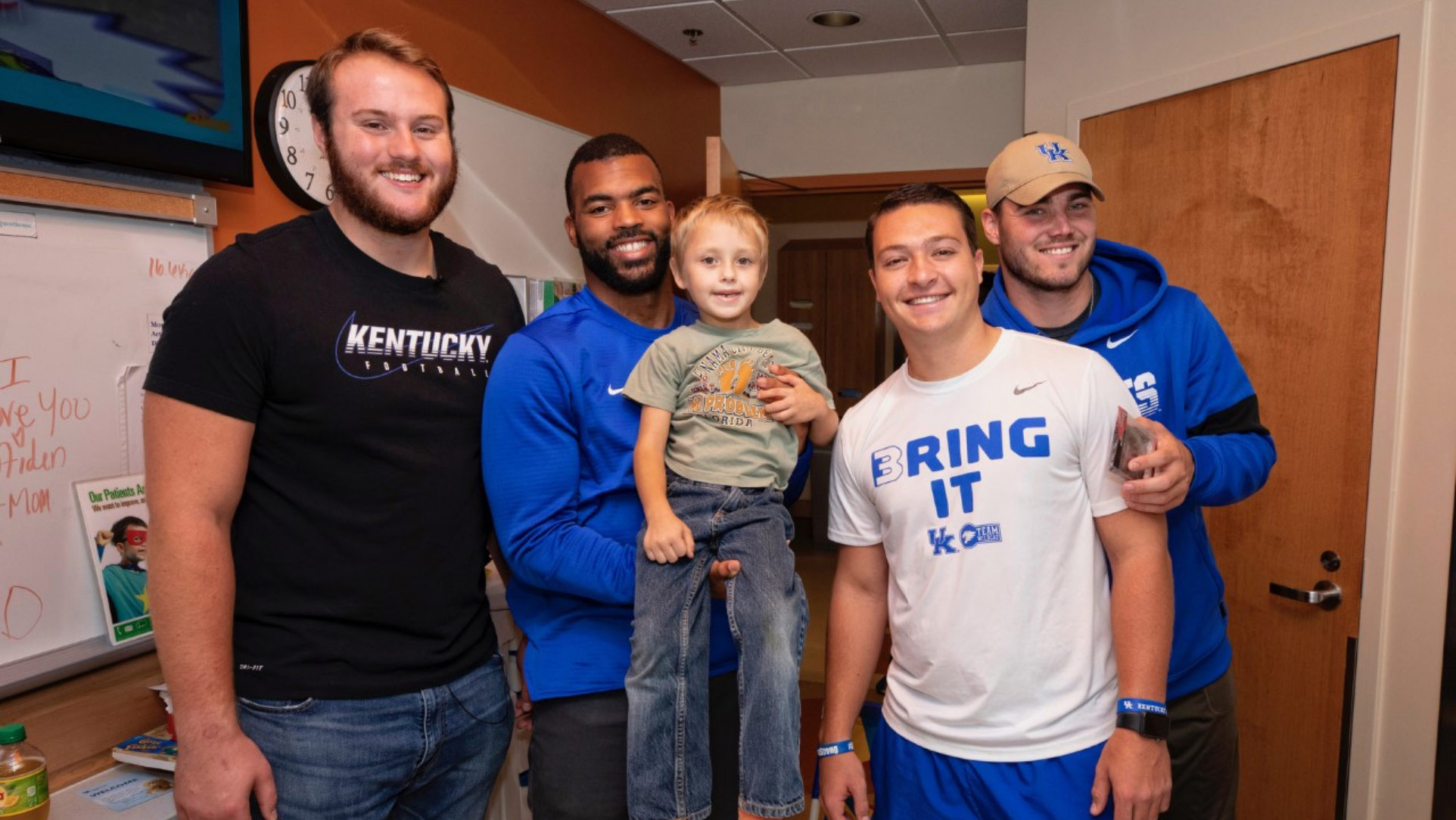Four football players pose in a hospital room. Courtney Love, a young-looking Black man in a blue shirt, holds a young boy who is a patient at Kentucky Children's Hospital.
