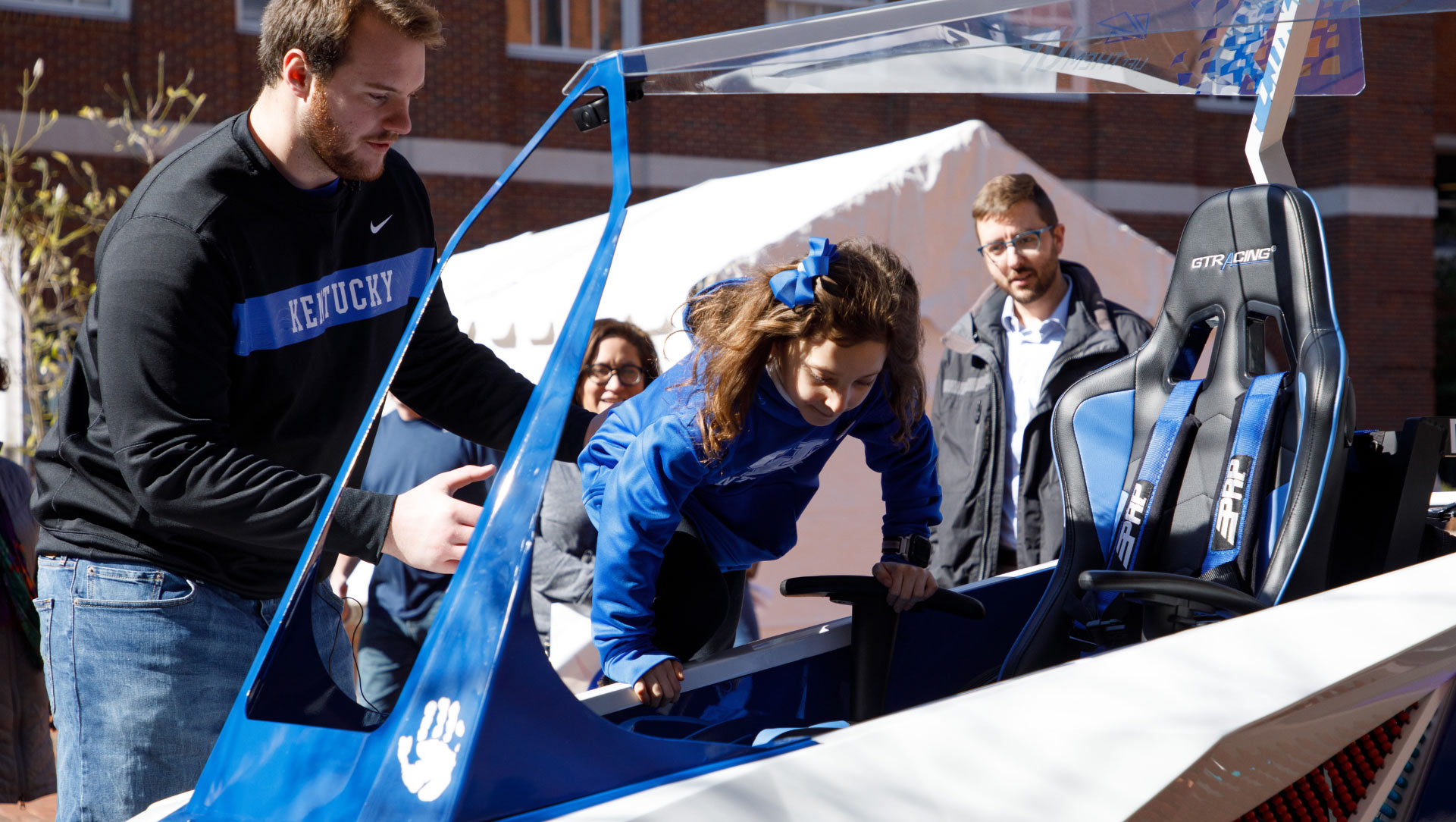 Luke Fortner, a young white man with a football player's build, brown hair, and a brown beard, helps a young girl into the cart. She is wearing UK blue and has a bow in her hair.