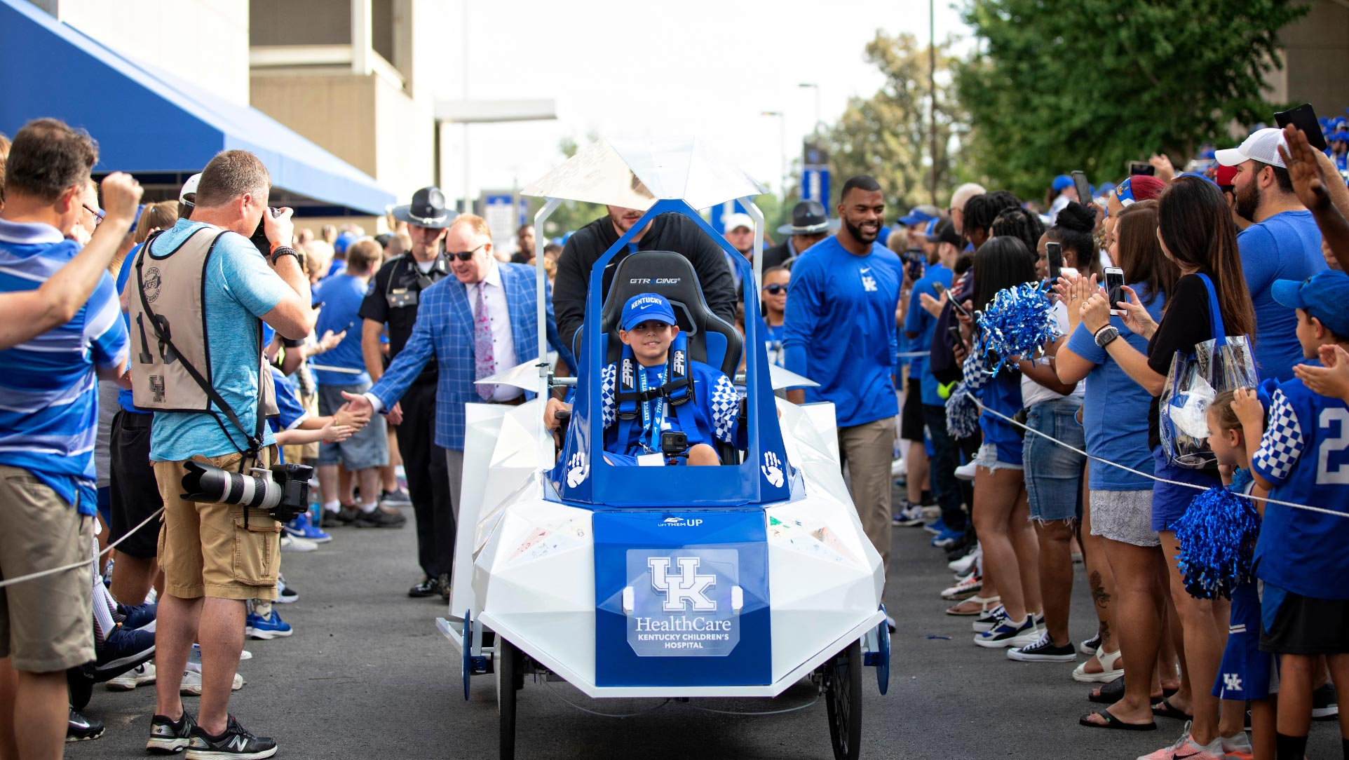 Maximo Shemwell, strapped into the cart, leads the football team down the Cat Walk between rows of cheering fans. Luke Fortner is pushing the cart. Coach Stoops and Courtney Love are visible to either side of the cart.