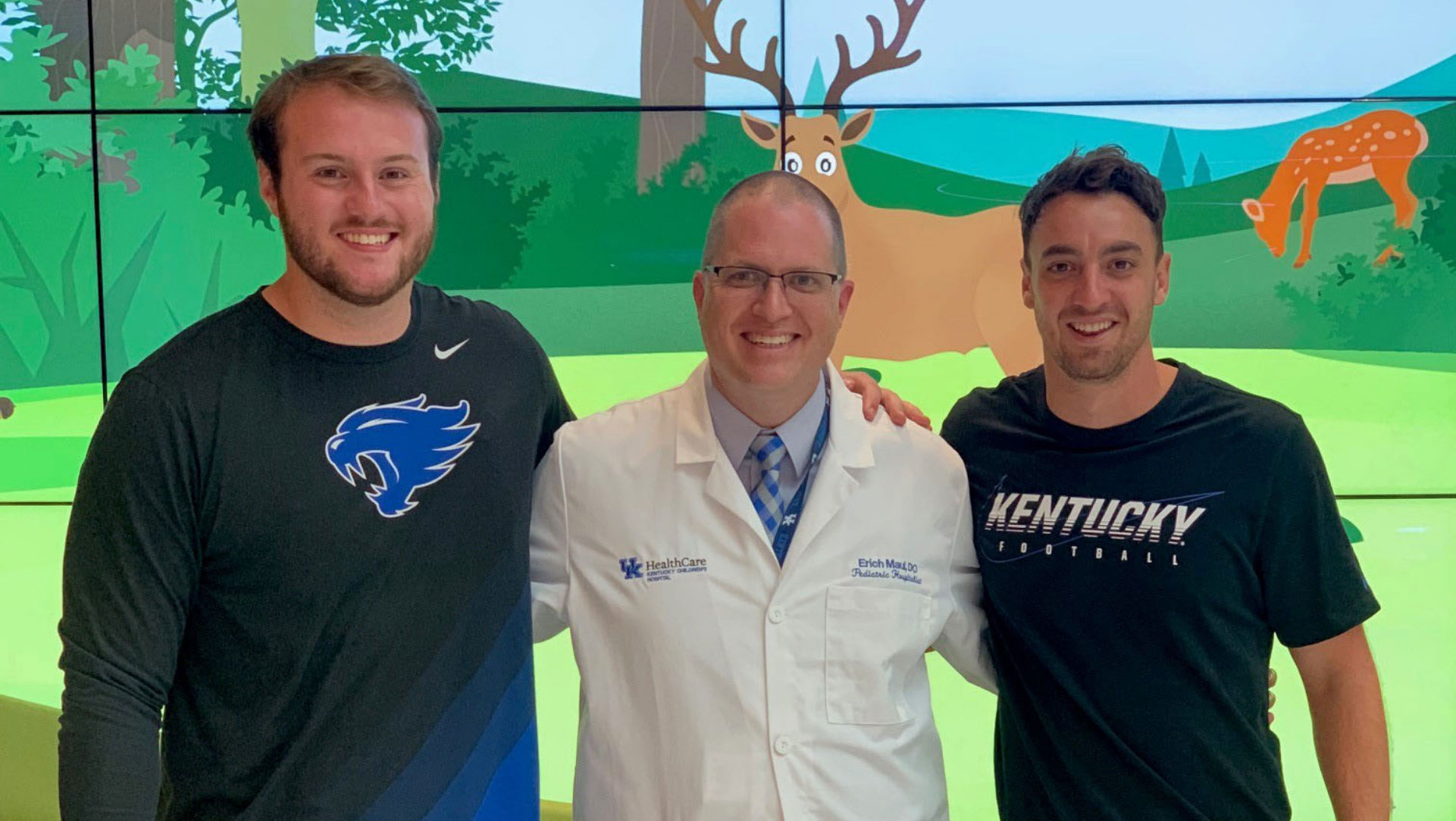 Luke and Max Duffy, a wiry-looking young white man with brown hair, pose for a photo with Dr. Erich Maul, a doctor in a white coat with glasses and short hair.