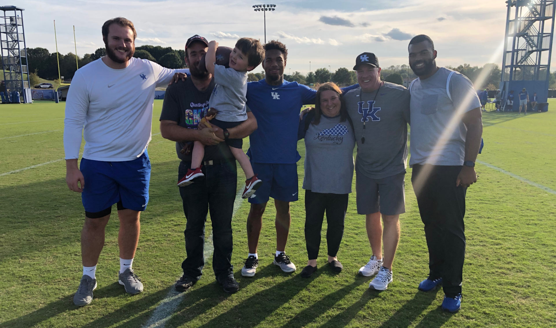 Six people pose for a photo on the football practice field. One man is holding Kase Chaney, an active kid who is holding a football. Coach Stoops, Courtney, and Luke are all in the photo, along with Kase's parents.