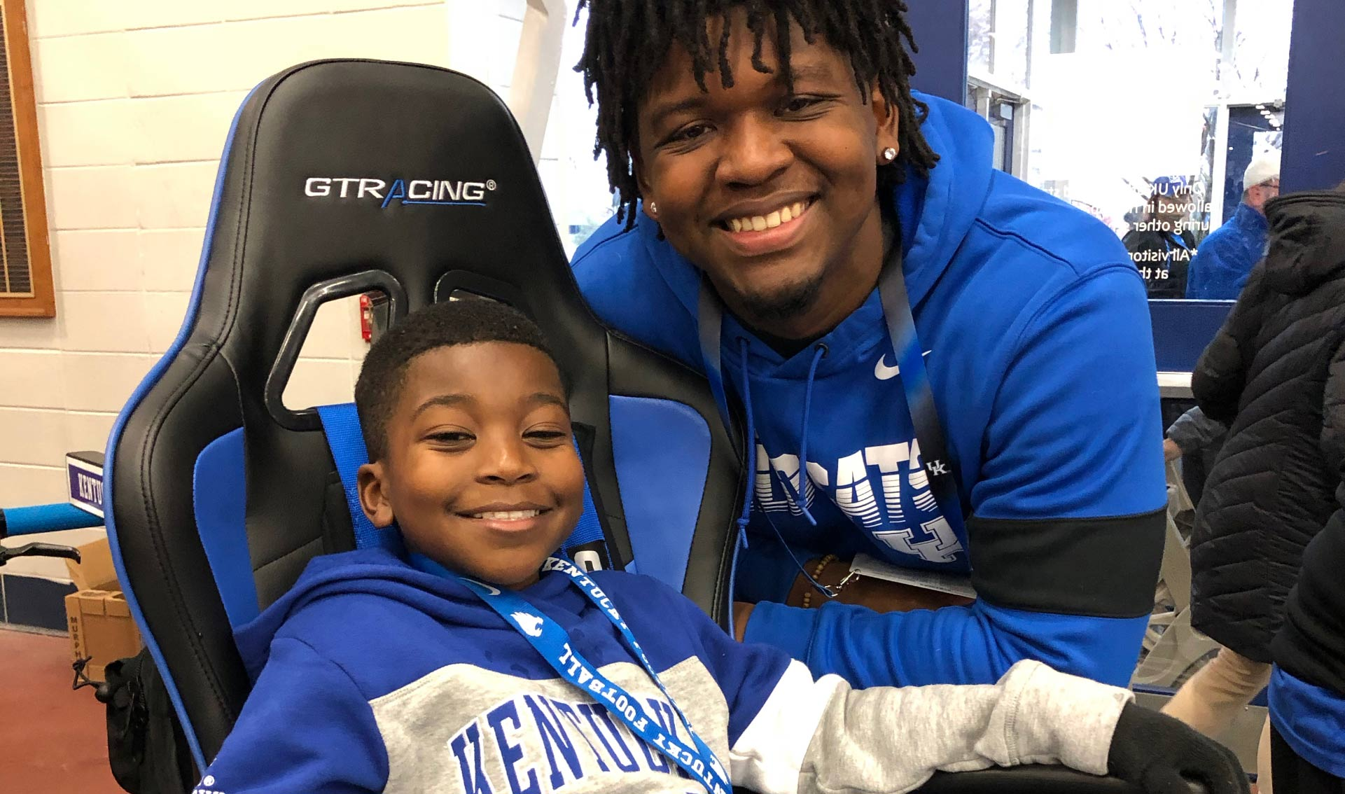 DJ Johnson, a young Black man in a Kentucky sweatshirt, poses for a close-up photo in the cart. A Black man on the UK football staff poses with him. Both are smiling.
