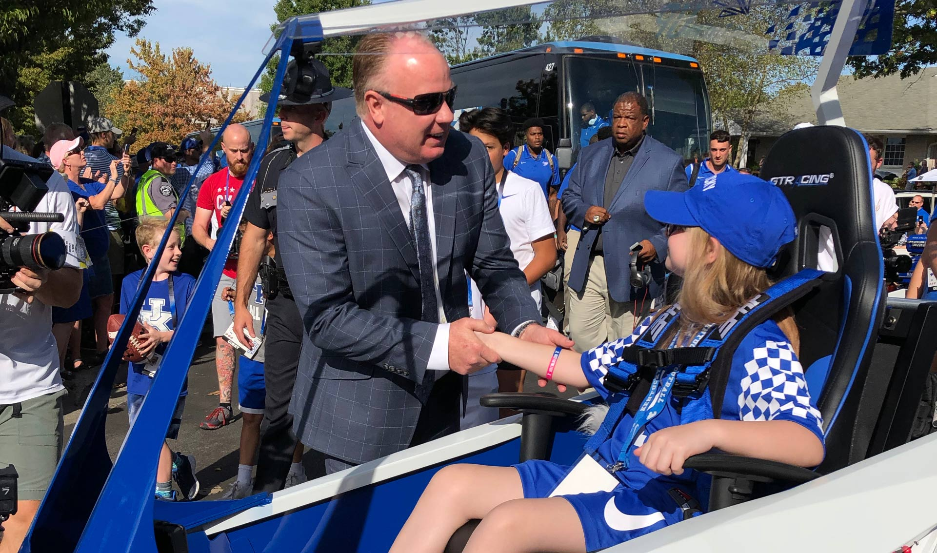 Coach Stoops shakes the hand of Audrey, a young white girl with blonde hair and a blue hat. She is sitting in the cart.