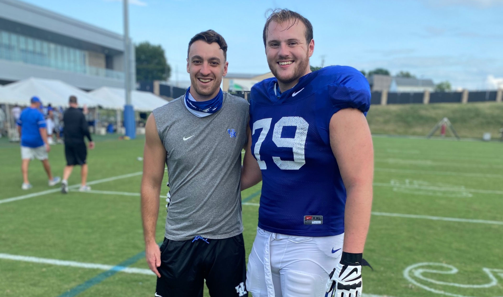 Luke and Max pose for a photo on the field. Both are wearing their practice gear and are smiling.