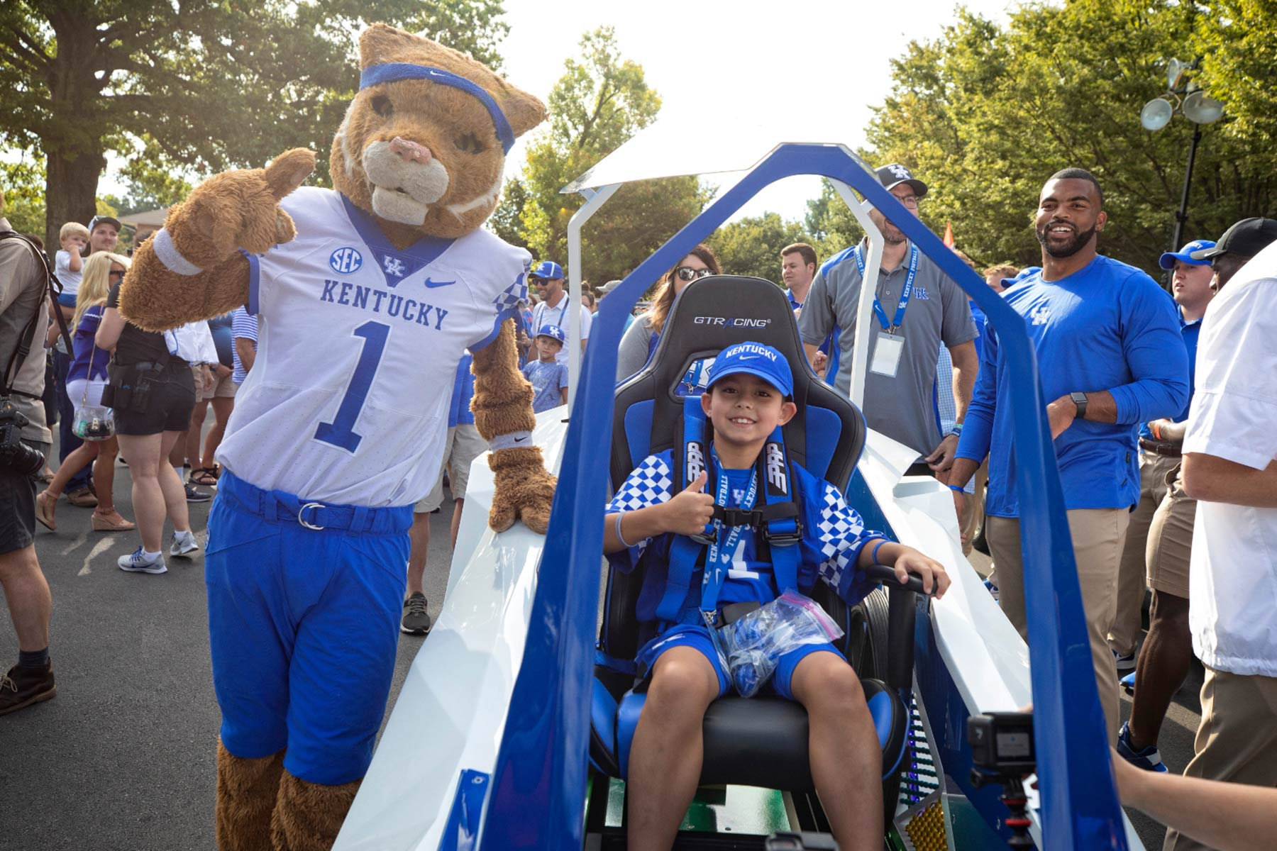 Maximo Shemwell, a young white boy dressed in UK gear, gives a thumbs up while he sits in a futuristic-looking open car. Next to him, the UK wildcat mascot waves.