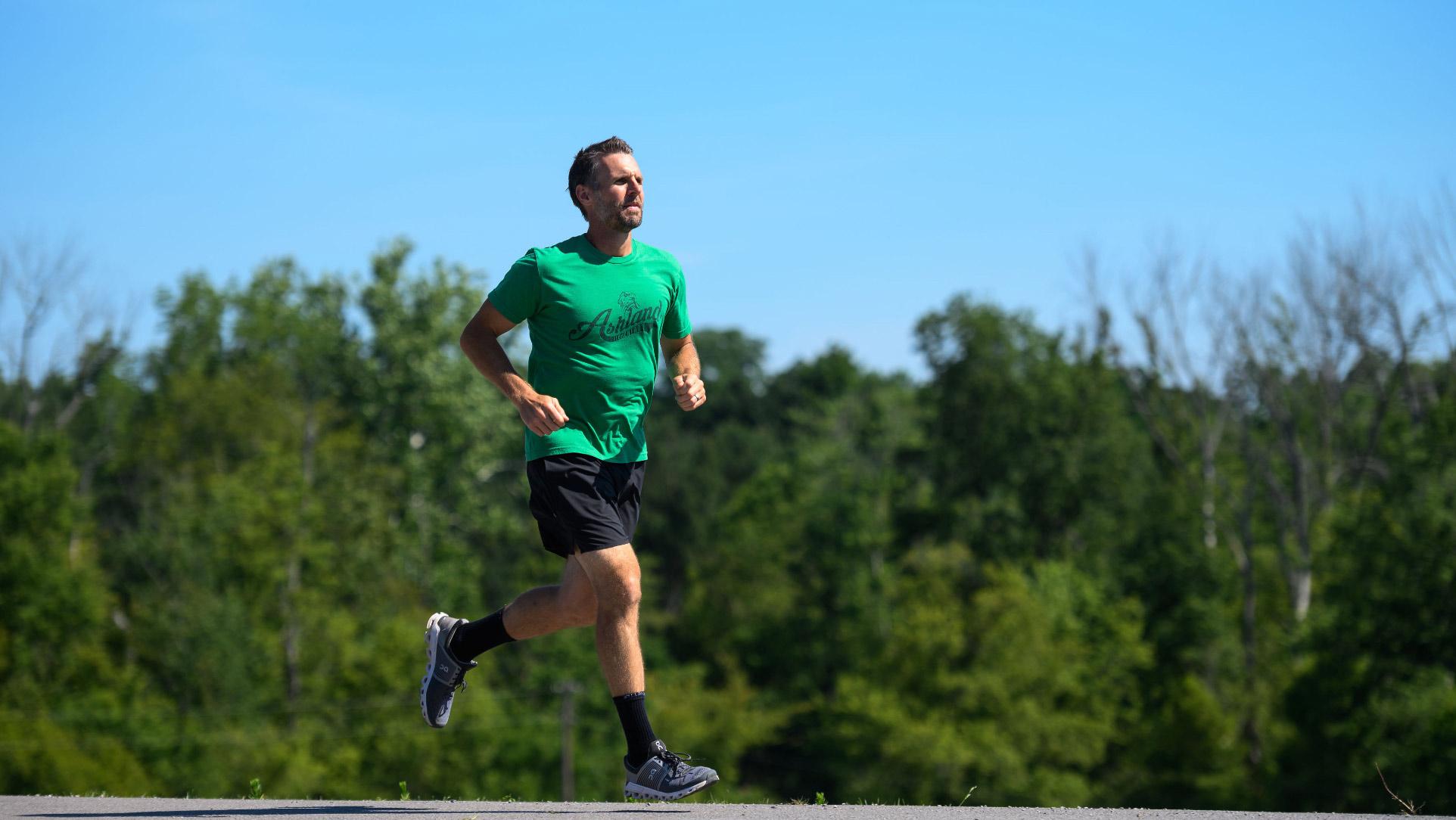 Ryan runs outside. He is wearing a green shirt, black shorts, and tennis shoes.