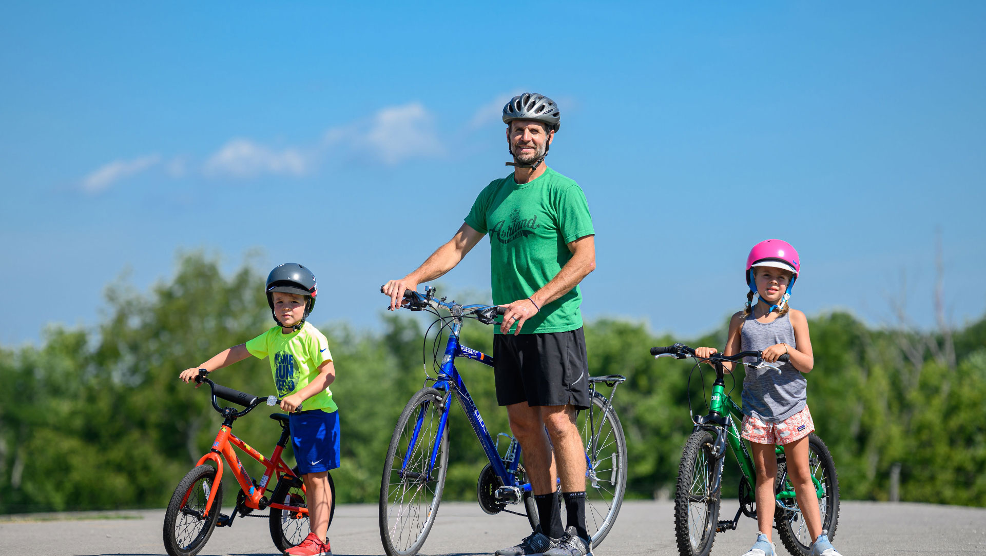 Ryan, wearing a helmet, stands next to a blue bicycle. He is flanked by his young son and daughter, who are both standing by their bicycles and wearing helmets.