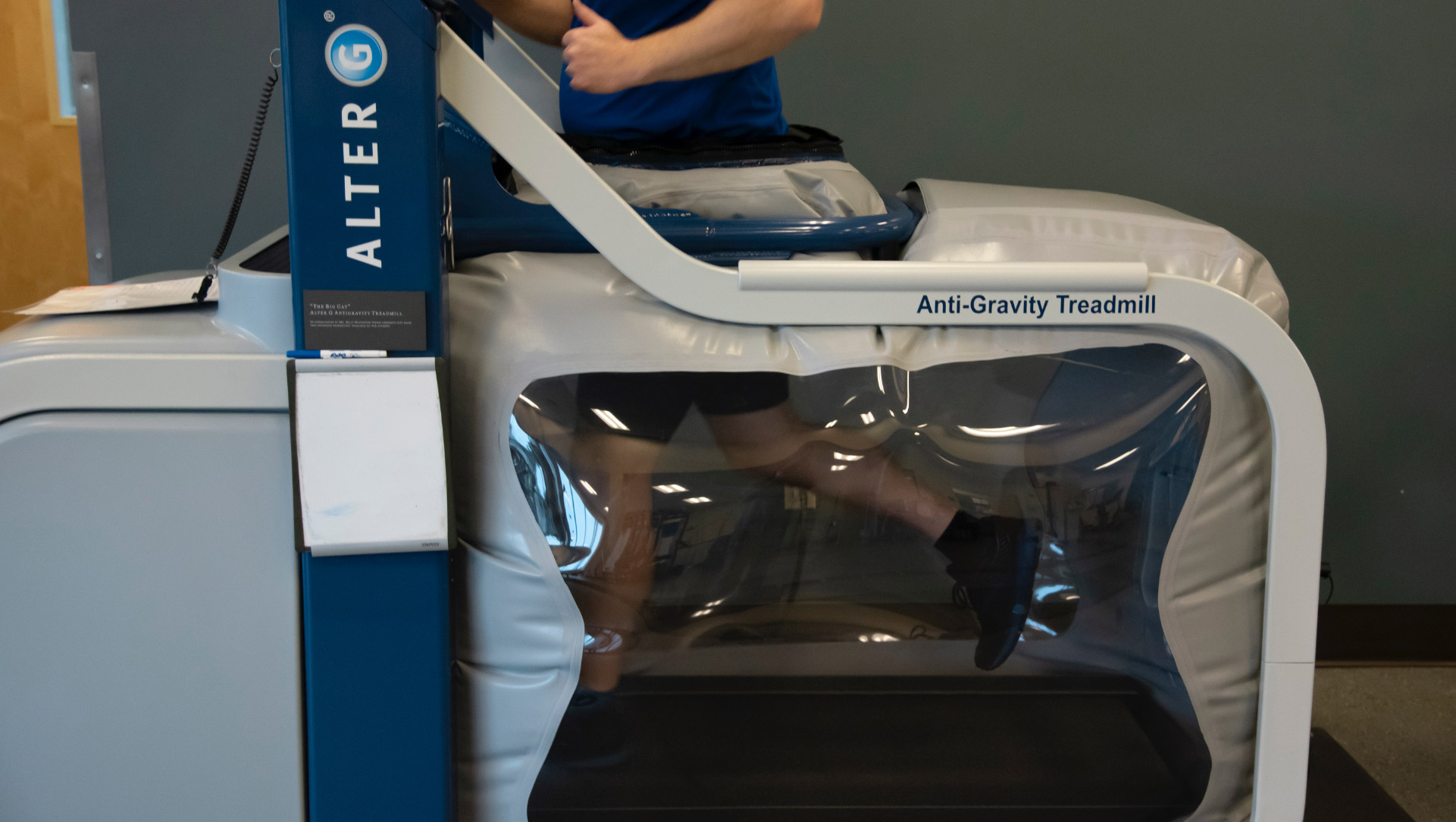 A photo of a person using the anti-gravity treadmill machine—the machine is built as a standard treadmill with gray plastic around the bottom half where the patient runs.