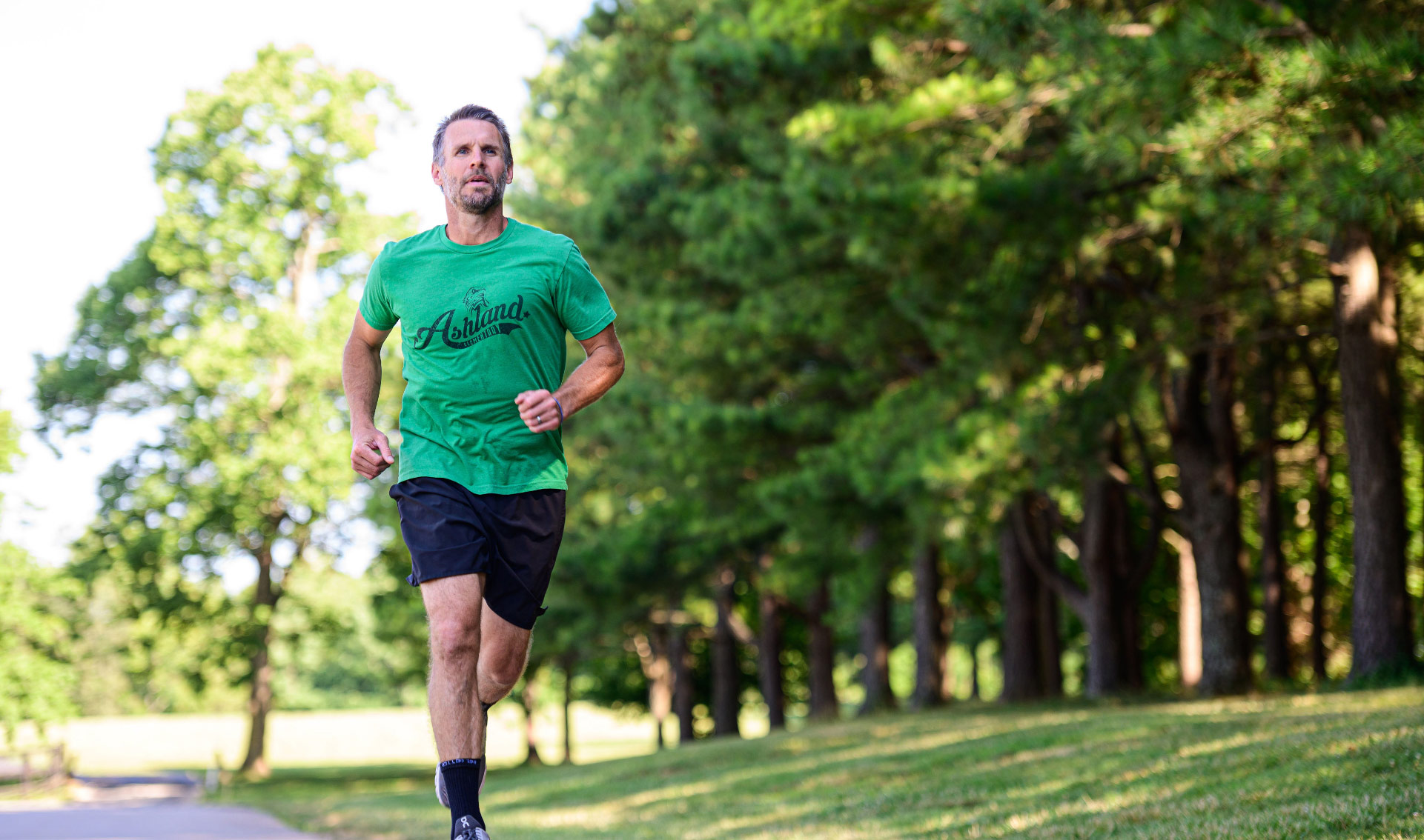 Ryan runs along a road next to a clump of trees. He is wearing a green shirt and black shorts.