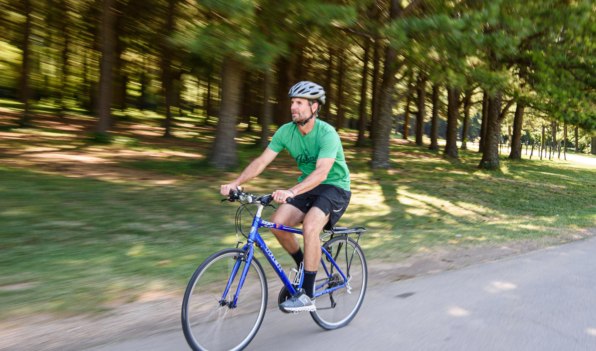 Ryan rides his bike along a road next to a clump of trees. The background is blurred slightly. He is wearing a green shirt and a helmet.