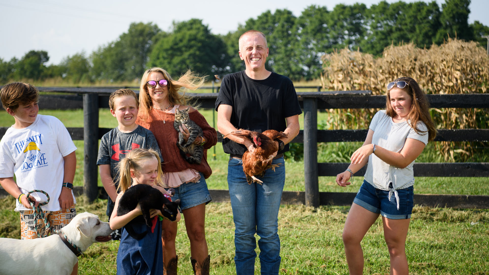 Dr. Day stands in the middle of the photo, holding a chicken that is trying to fly away. His wife and four children stand around him, holding cats and a family dog. Dr. Day is smiling despite the chaos around him.