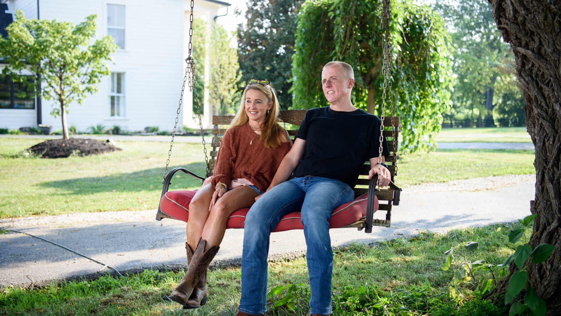 Dr. Day and his wife, a slim woman with long blonde hair wearing jean shorts, a long-sleeved orange blouse, and cowgirl boots, sit on a wooden bench swing together.