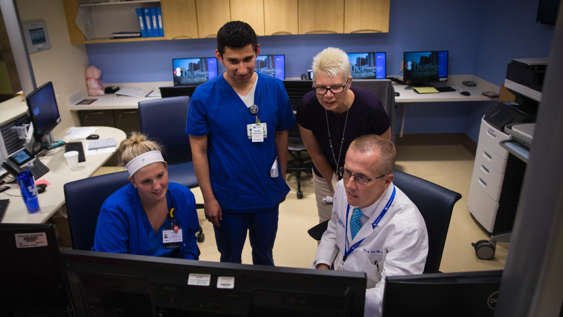Dr. Day, dressed in a white doctor's coat and tie, sits in a chair as he looks at a computer with three of his co-workers sitting and standing next to him.