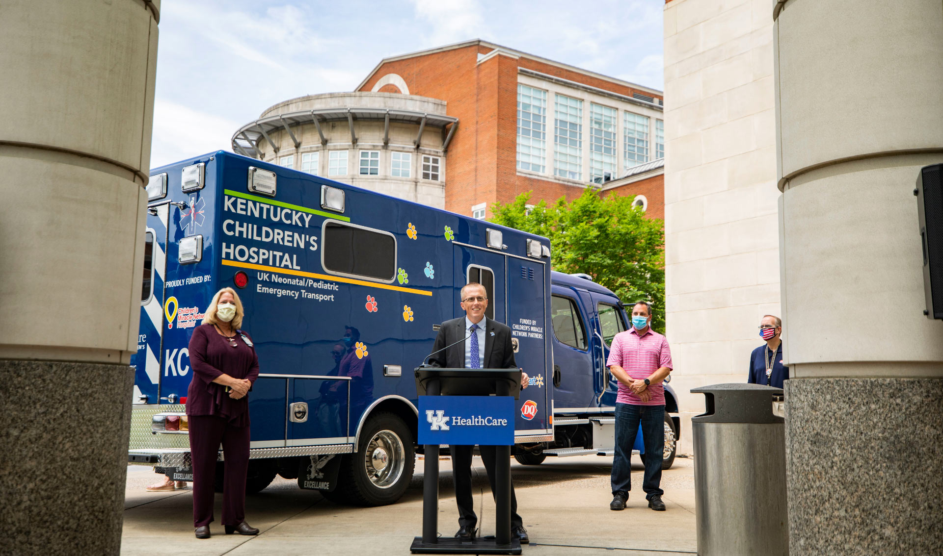Standing behind a podium outside of the hospital in front of a blue Kentucky Children's Hospital ambulance—Dr. Day prepares to speak to his colleagues and the community. He is dressed in a black suit with a blue shirt and blue tie.