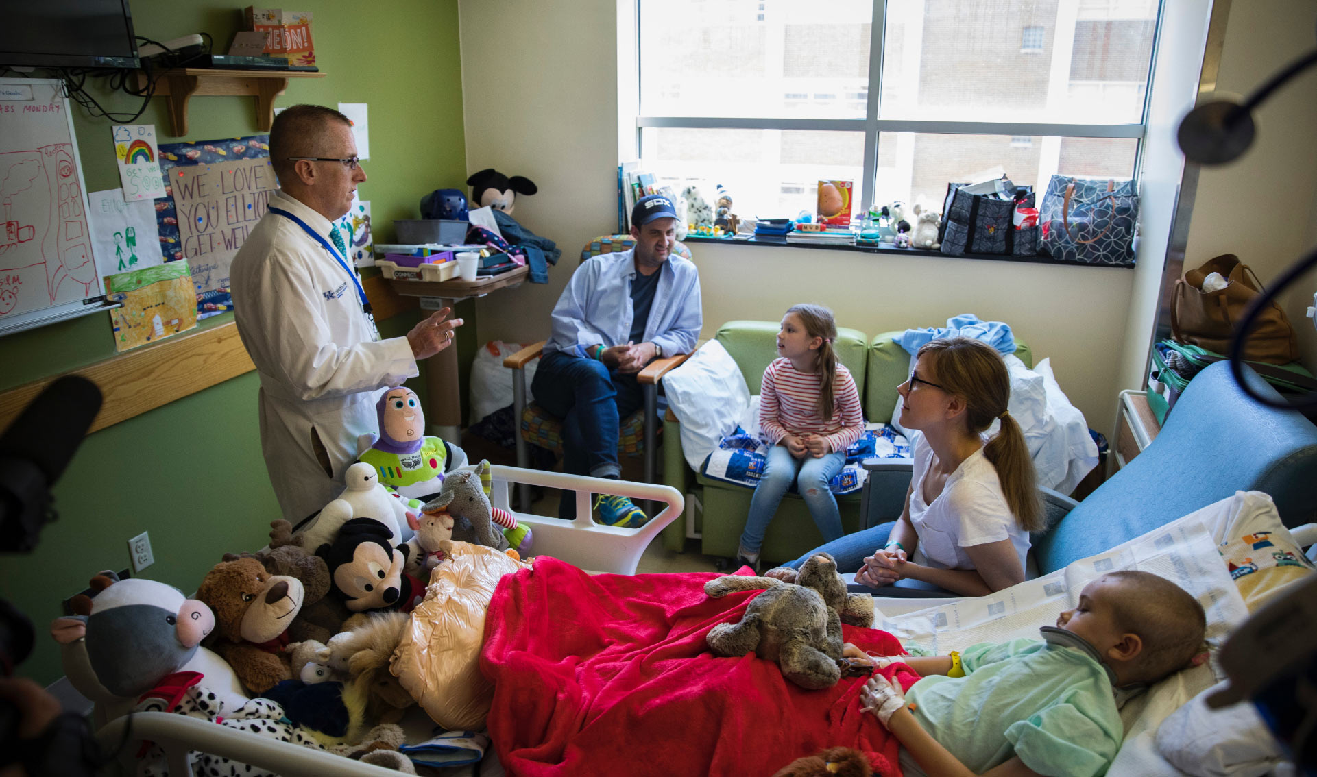 Dr. Day stands in a young patient's room speaking to their family—the room is filled with posters, drawings, toys and stuffed animals.
