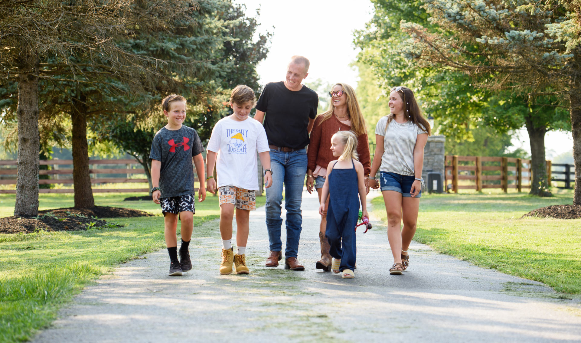 Dr. Day and his family walk down the driveway of their house together as they all smile while looking towards Dr. Day.