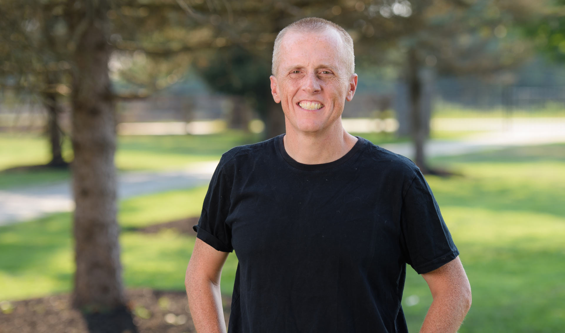 A portrait photo of Dr. Day smiling with greenery in the background. He is wearing a plain black t-shirt and is standing with his hands on his hips.