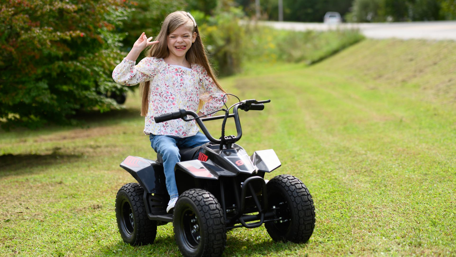 Taytum sits on a tiny ATV. She's wearing a floral top and jeans and her waist-length hair is loose. She's smiling, her tongue is out, and she's flipping a peace sign to the camera.