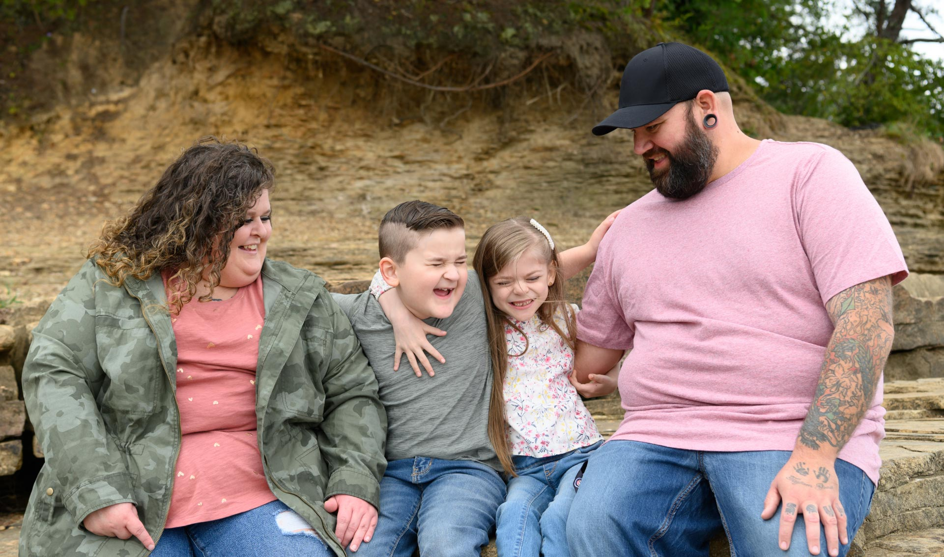 Taytum and her family all laugh as they hug each other. They are sitting on some rocks in an outdoor setting.
