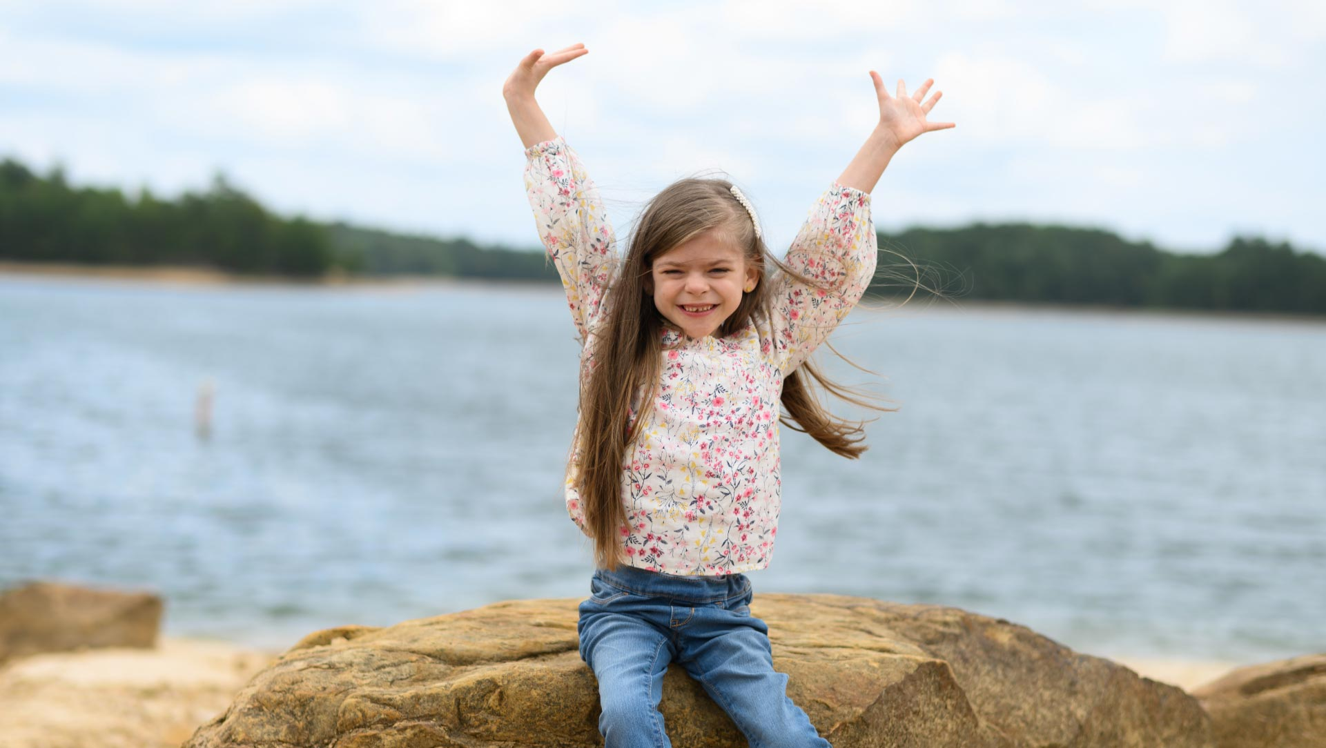 Taytum sits on a rock next to the lake. She holds her hands up in the sky and grins.
