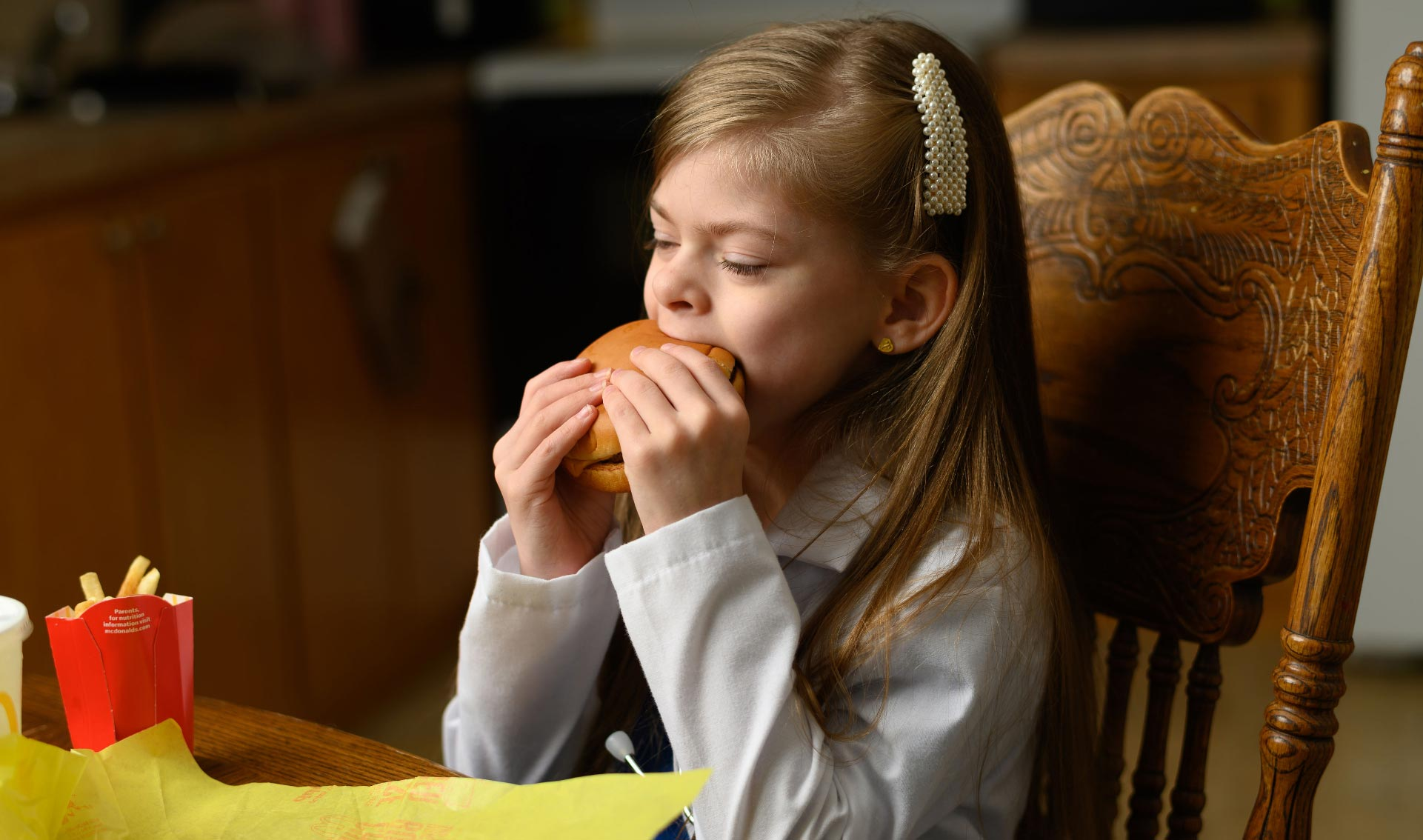 Taytum chomps down on a McDonald's cheeseburger, held in both hands. She is still wearing her white coat and scrubs.