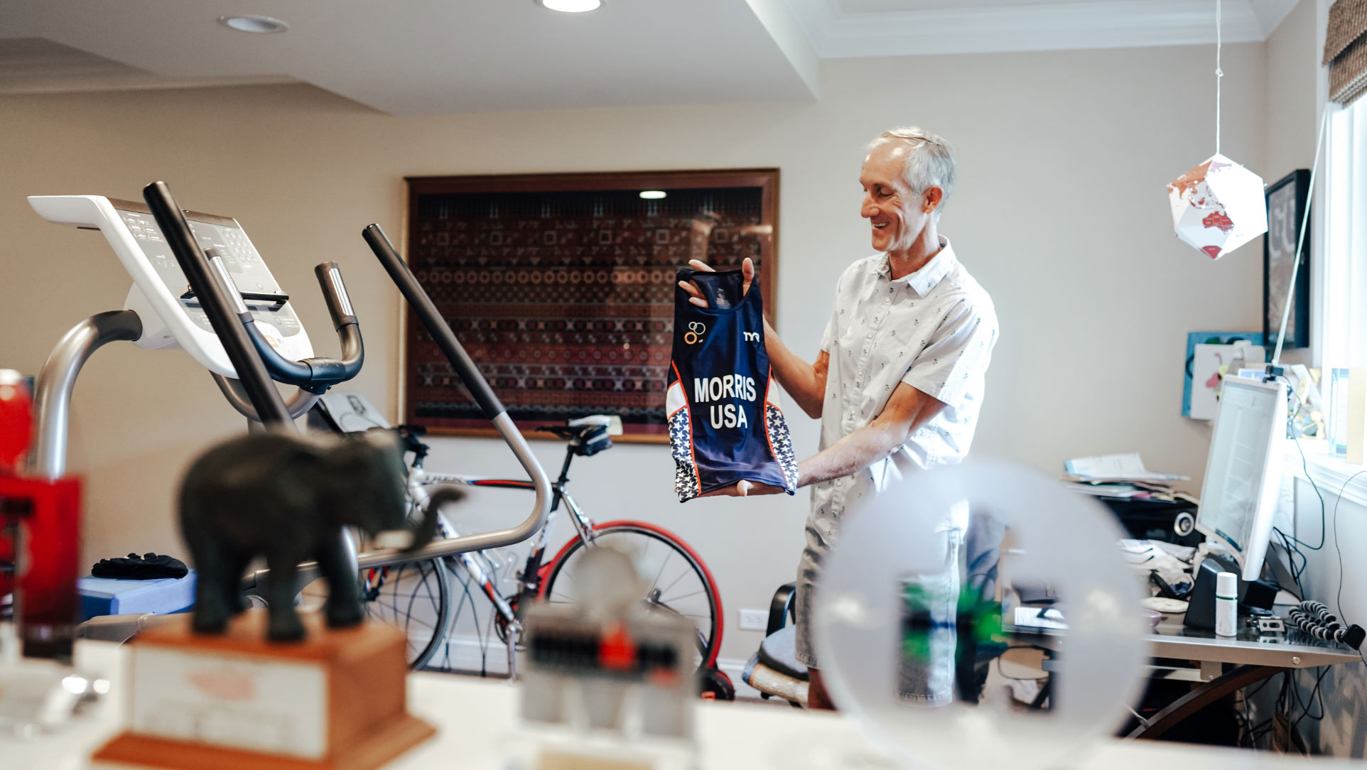 Doug, wearing a white button-down, smiles as he holds up a cycling jersey that says MORRIS USA. He is inside his home, in a space with a bike and some workout equipment.