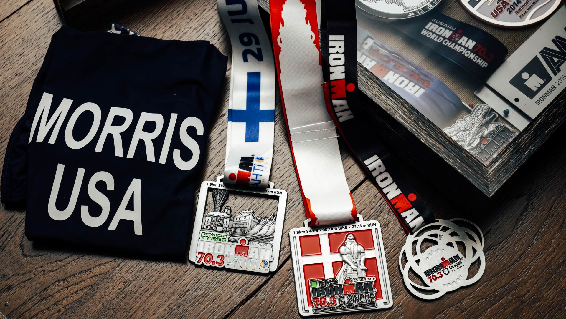 Several IRONMAN medals and mementoes of past races sit on a table.