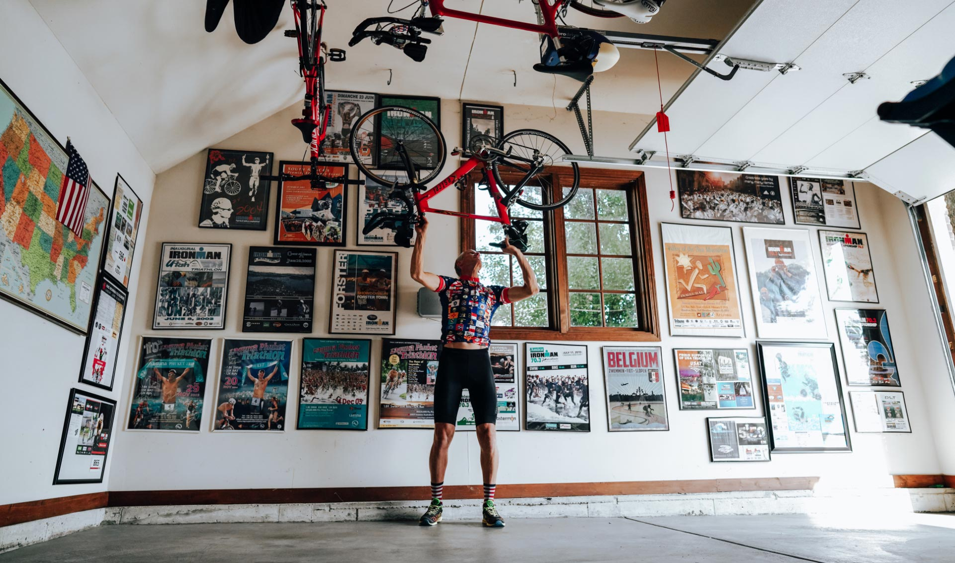 Doug lifts his bike above his head to hang it up on hooks in his garage.