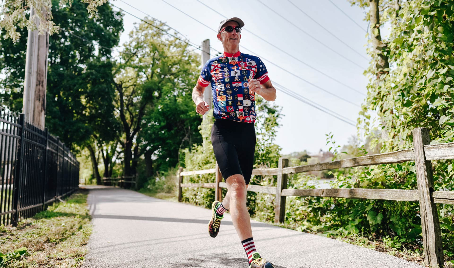 Doug, wearing the flag-print jersey, black bike shorts, and red and white striped socks, grins as he runs down a sidewalk. He is wearing a baseball hat and sunglasses.