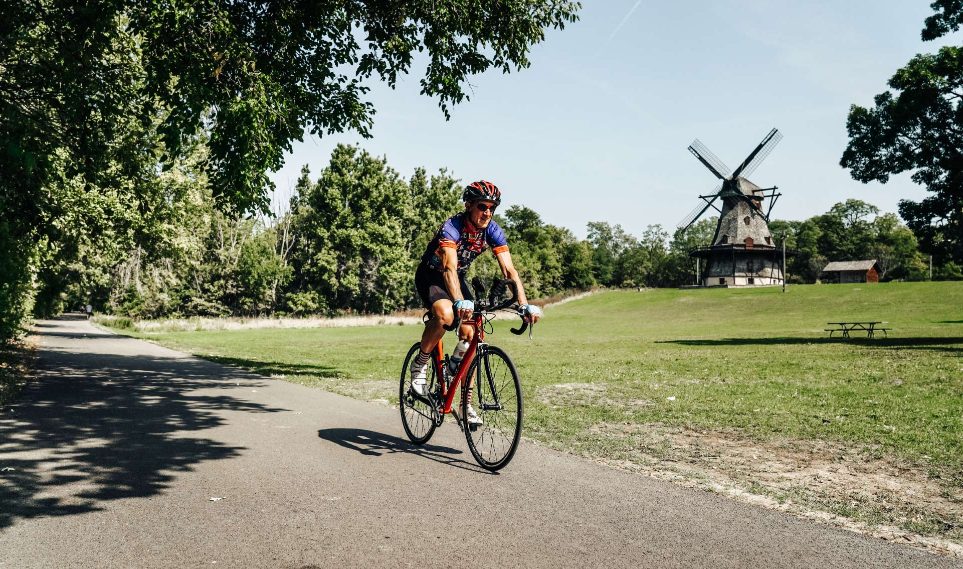 Doug rides his bike past a windmill in a rural outdoor setting.