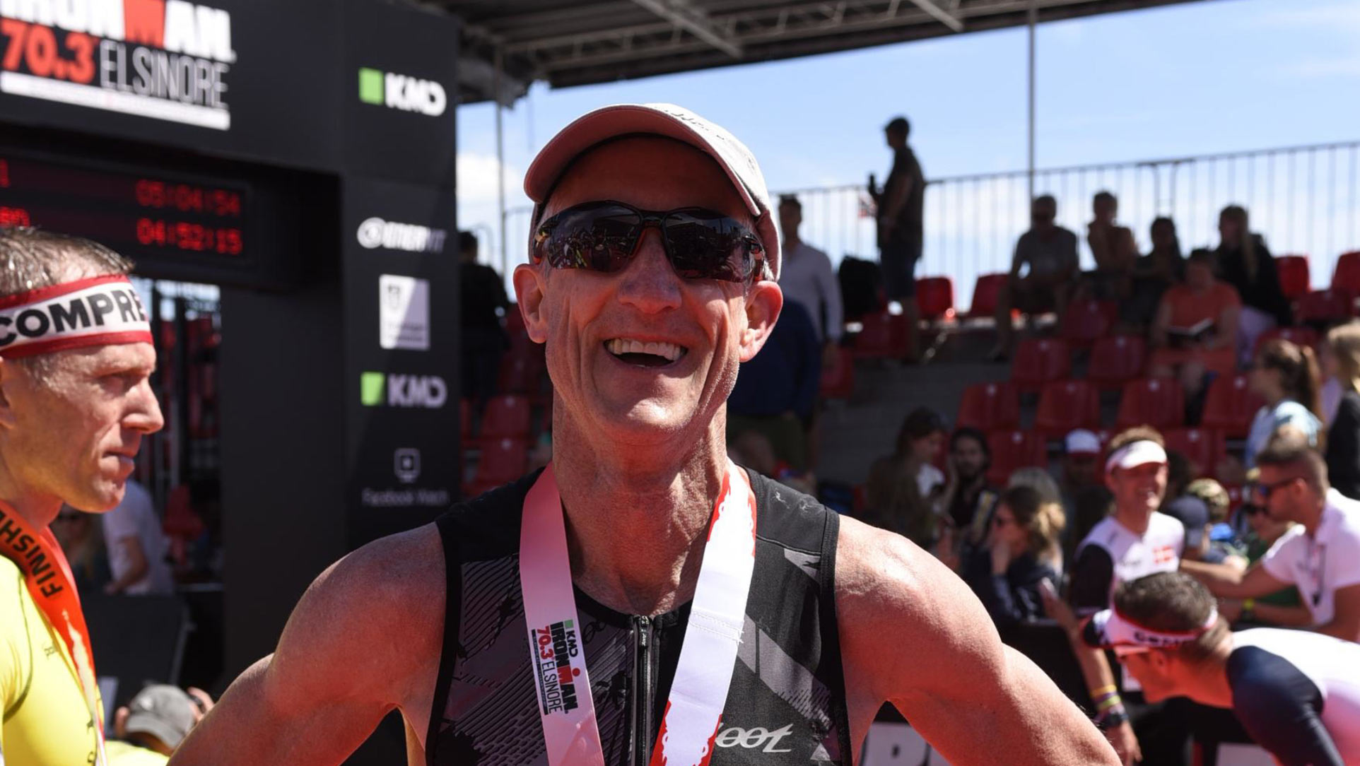 Doug smiles widely after receiving a medal at a triathlon. He is wearing a black unitard, sunglasses, and a baseball hat.