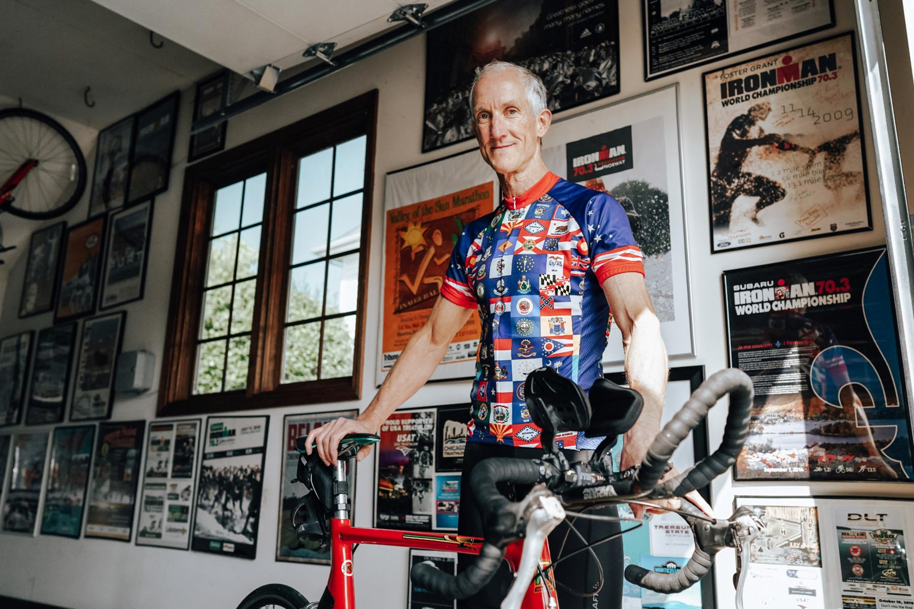 Doug Morris, a tall, wiry, older white man wearing a cycling jersey covered with international flags, stands behind a bike in his home. The wall behind him is covered in triathlon posters.