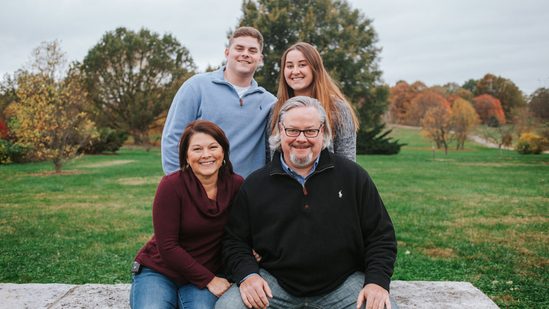 Jill, her husband, her son and her daughter pose for a group shot in an outdoor setting.