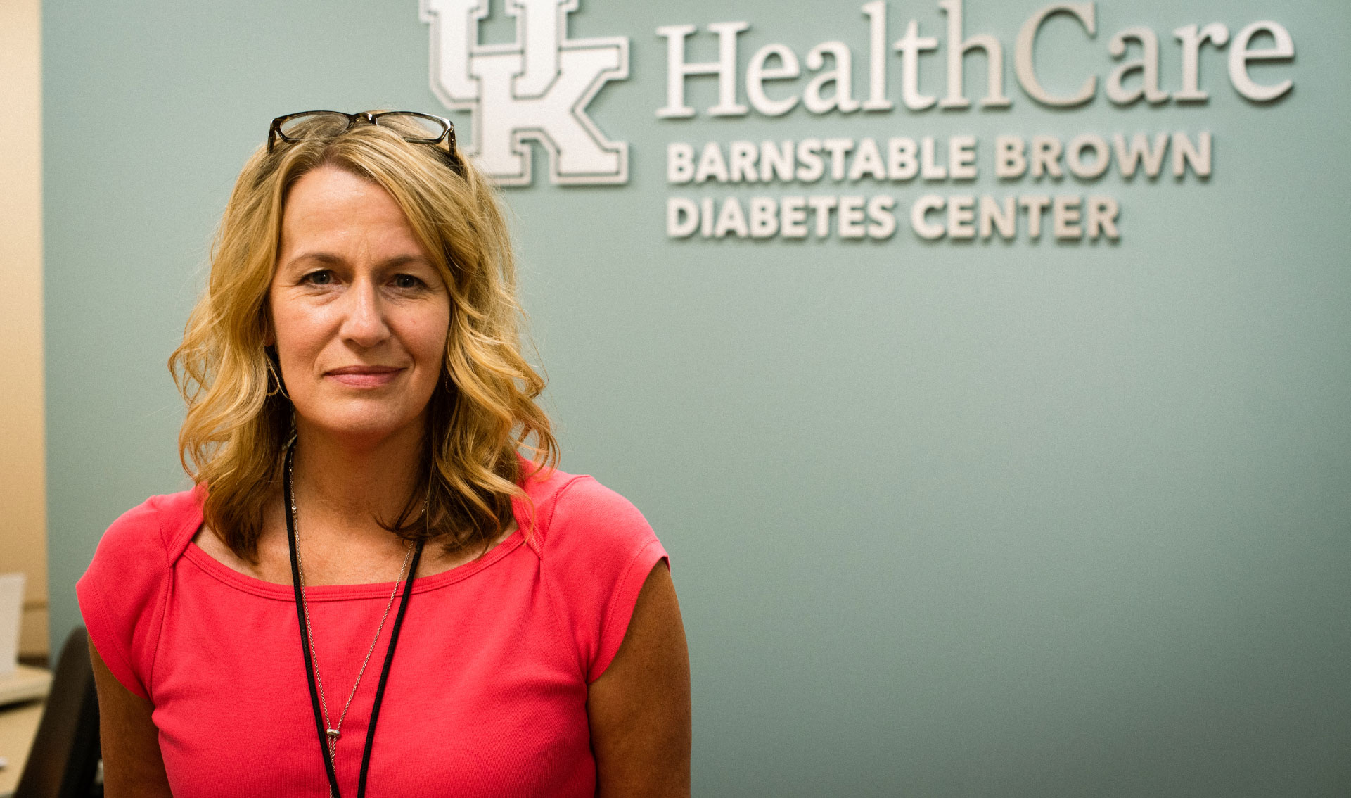 Sheri Setser-Legg, a middle-aged white woman with curled blonde hair, stands in front of a UK HealthCare Barnstable Brown Diabetes Center sign. She is wearing a pink top, has her glasses on top of her head, and is smiling very slightly.