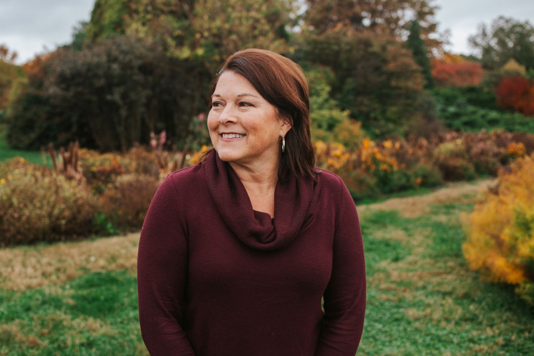 Jill Blake, a middle-aged white woman with brown hair, stands in an outdoor setting and smiles while she looks away from camera. She is wearing a dark red sweater.