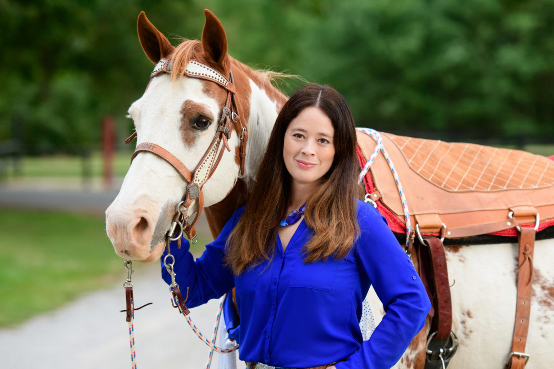 Miko McFarland, an Asian-American woman with long dark hair, stands next to a white horse with brown splotches. Miko is wearing a blue top and is smiling slightly.