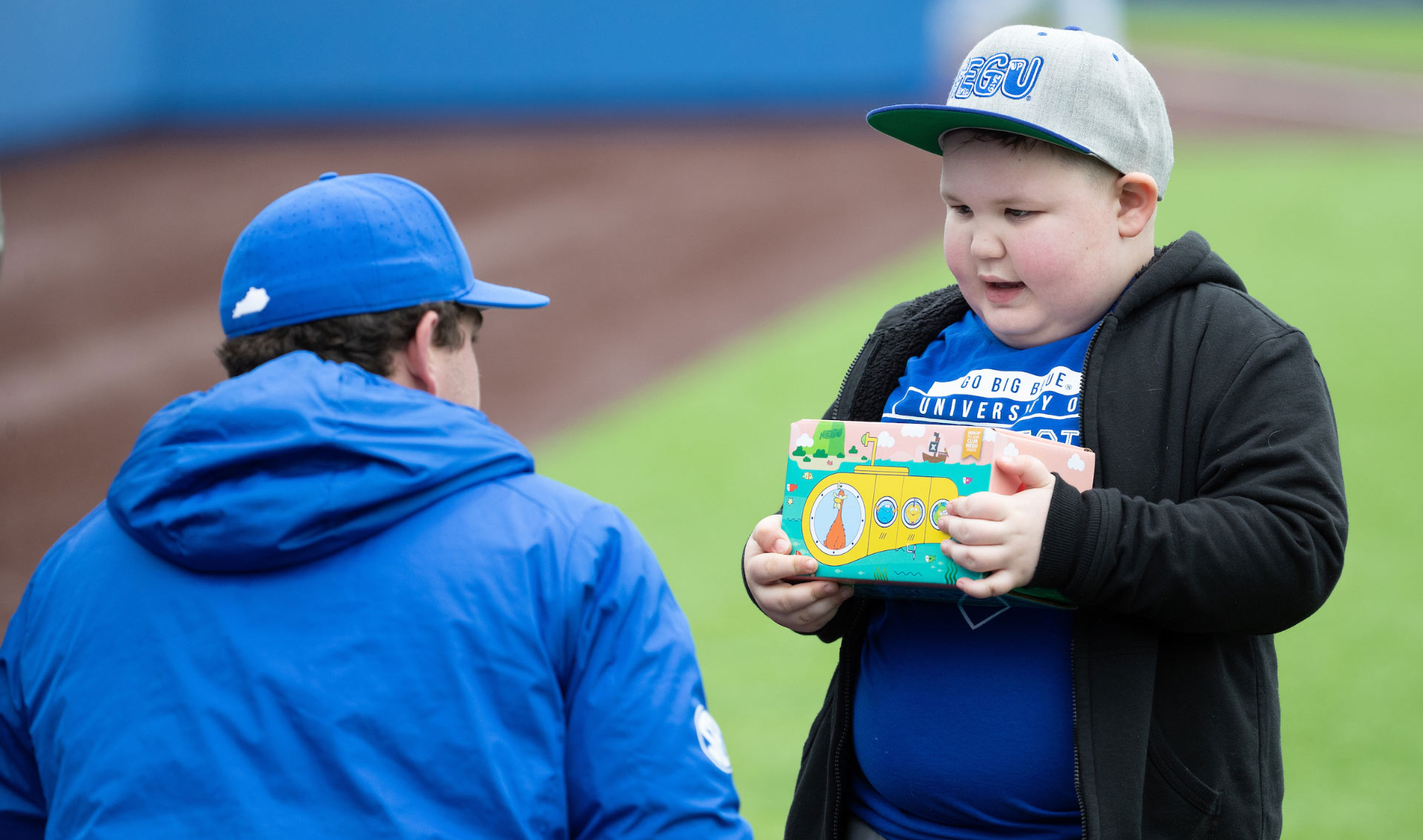 T.J. crouches down to talk to a young kid wearing a baseball hat. The kid is holding a brightly-colored box. T.J. is wearing a baseball cap and a blue jacket.
