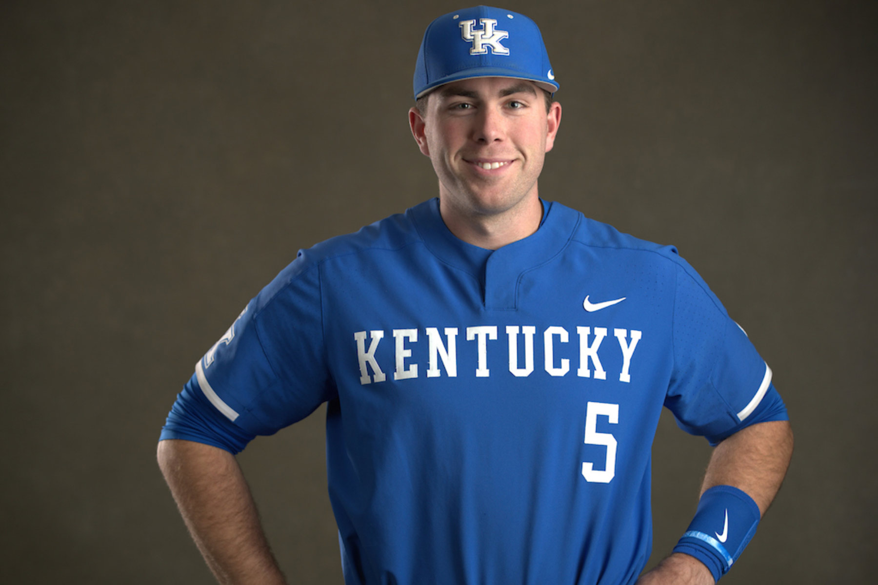 T.J. Collett, a young white man with brown hair, poses for a portrait against a gray backdrop. He has a Kentucky baseball uniform on, is standing with his hands on his hips, and is smiling.