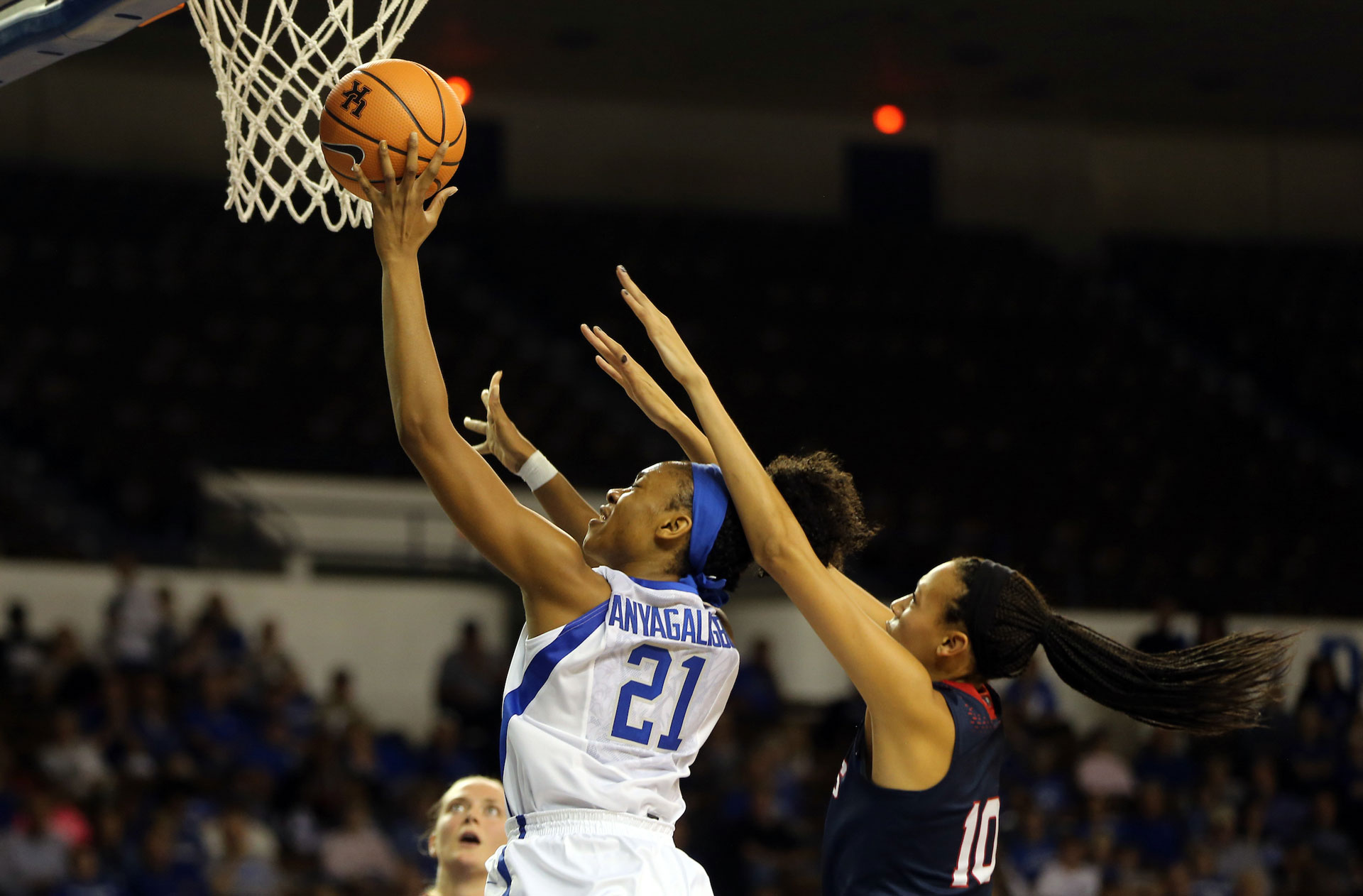 An action shot of Ogechi during a game, jumping up to the basket with a basketball in her hand and an opposition defender behind her.