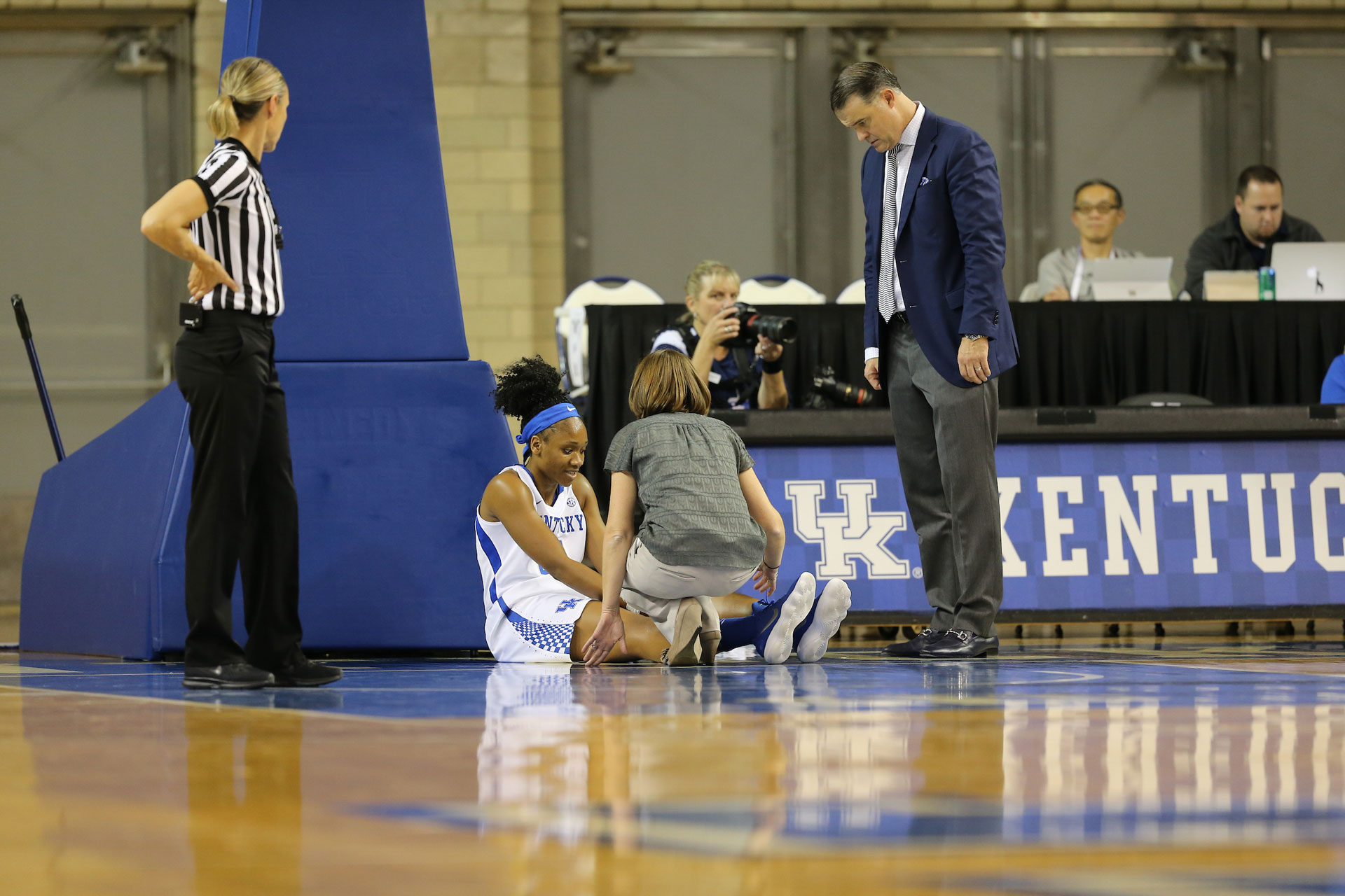Ogechi sits at the edge of the court, surrounded by Coach Matthew Mitchell, the team physician, and a referee. Ogechi is holding her knee and has her legs straight out in front of her.