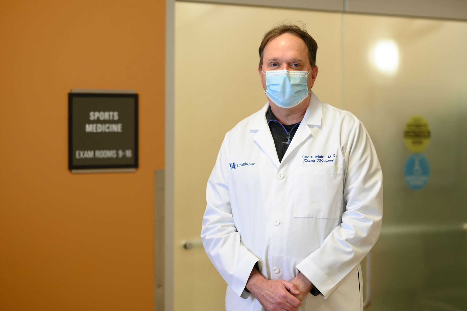 A portrait of Dr. Scott Mair, a middle-aged white man with brown hair and a white lab coat. He is standing next to a door labeled Sports Medicine Exam Rooms and is wearing a blue surgical mask.