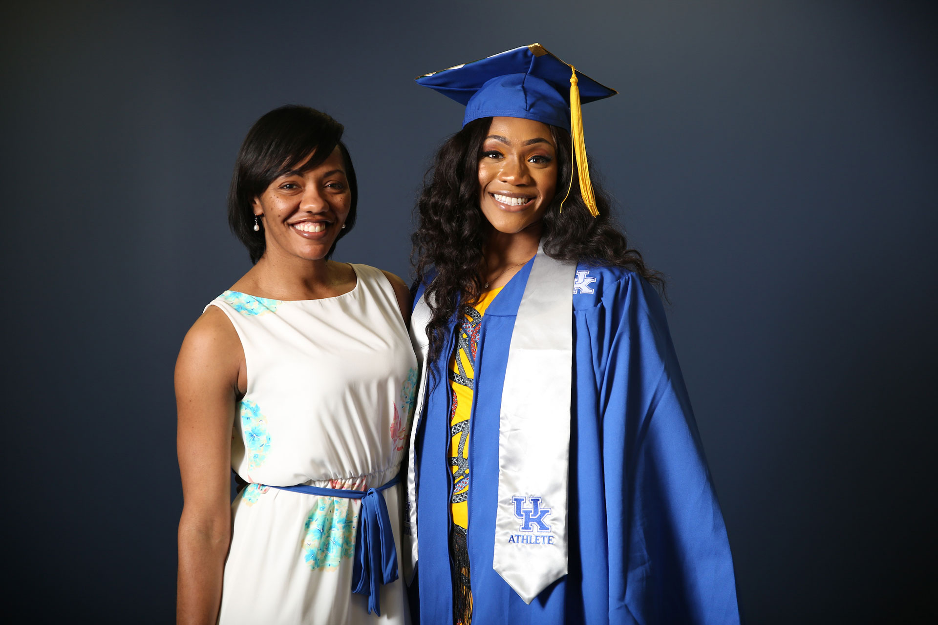 Ogechi poses for a photo in her graduation cap and gown, a yellow dress under her robes, and a silver UK Athlete stole. She is smiling broadly and her hair is loose and curled. Standing next to her is Tiffany Hayden, former Women's Basketball academic advisor and current Assistant Athletic Director for Diversity, Equity and Inclusion. Tiffany, a young-looking Black woman, is wearing a white dress with floral print and is smiling.