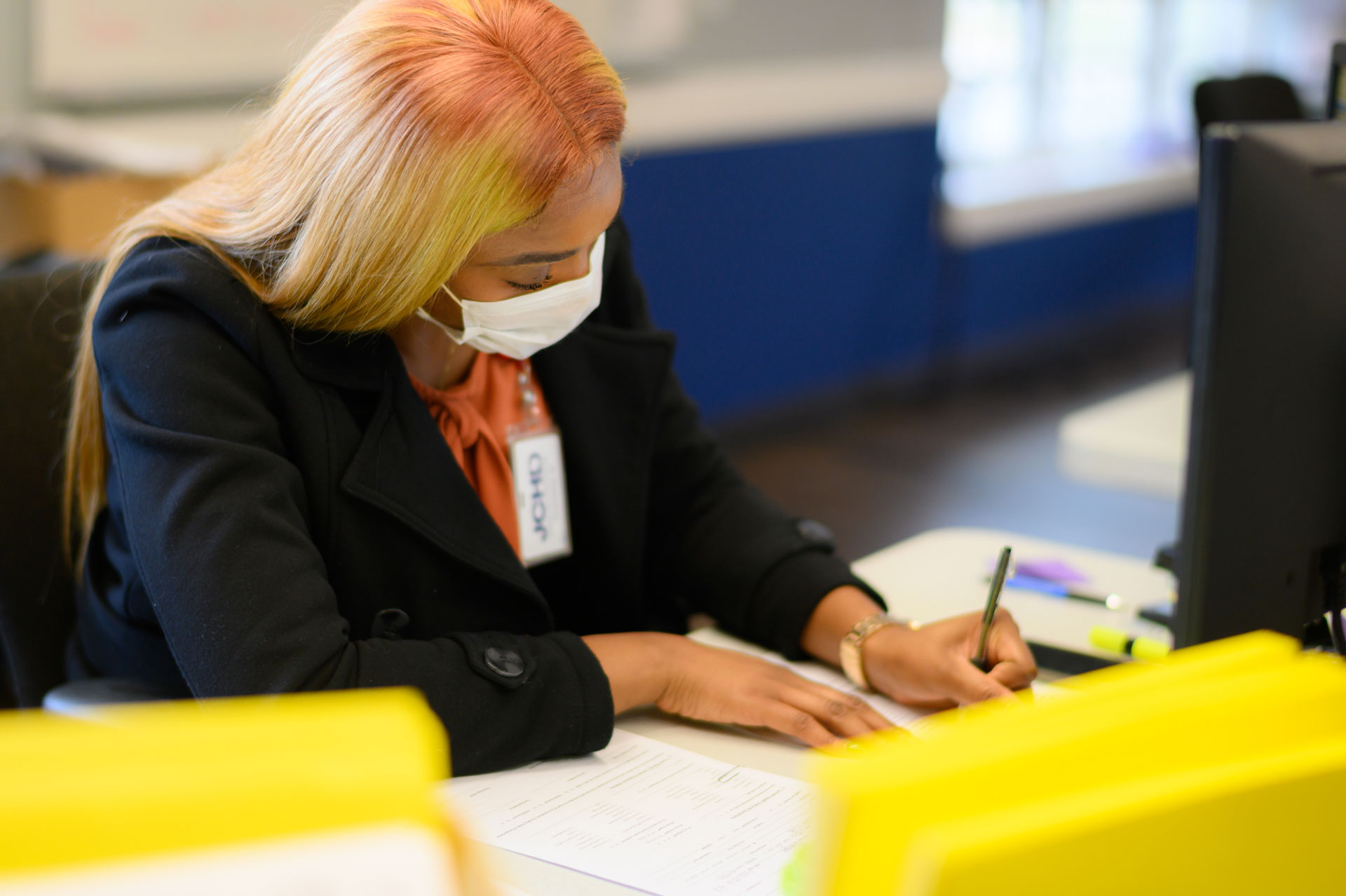 Ogechi, dressed in a black blazer and orange blouse, works at a desk at the UK HealthCare Sports Medicine clinic. Her hair is long, straight, and blonde.