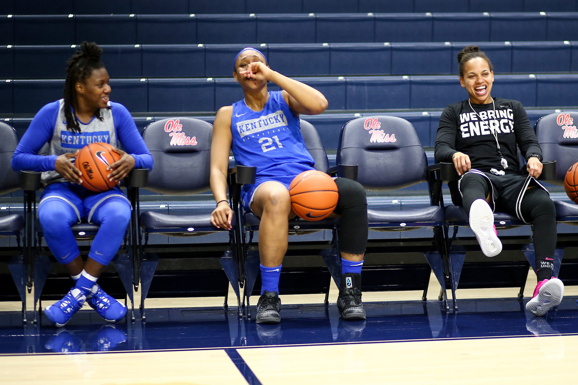 Ogechi sits on the sidelines, wearing a knee brace and a UK jersey. She is laughing and holding a hand up to her mouth. Coach Amber Smith is sitting to one side of her and is also laughing. Another teammate is sitting on the other side of Ogechi and is grinning at both of them.