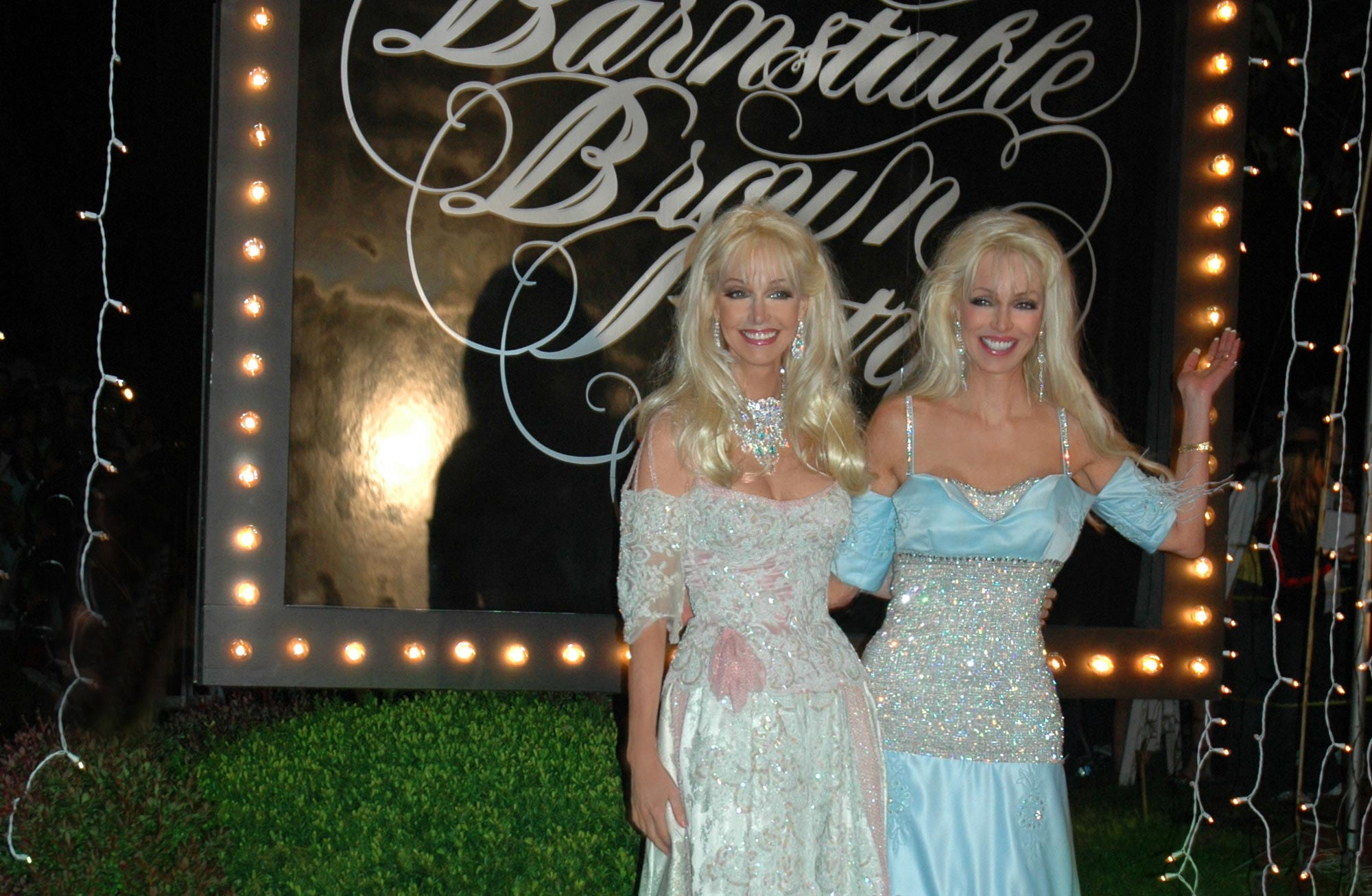 Patricia Barnstable-Brown and her twin sister, Priscilla—identical middle-aged white women with blonde hair—stand in front of a lit sign reading Barnstable Brown Party. Both are wearing elegant dresses.