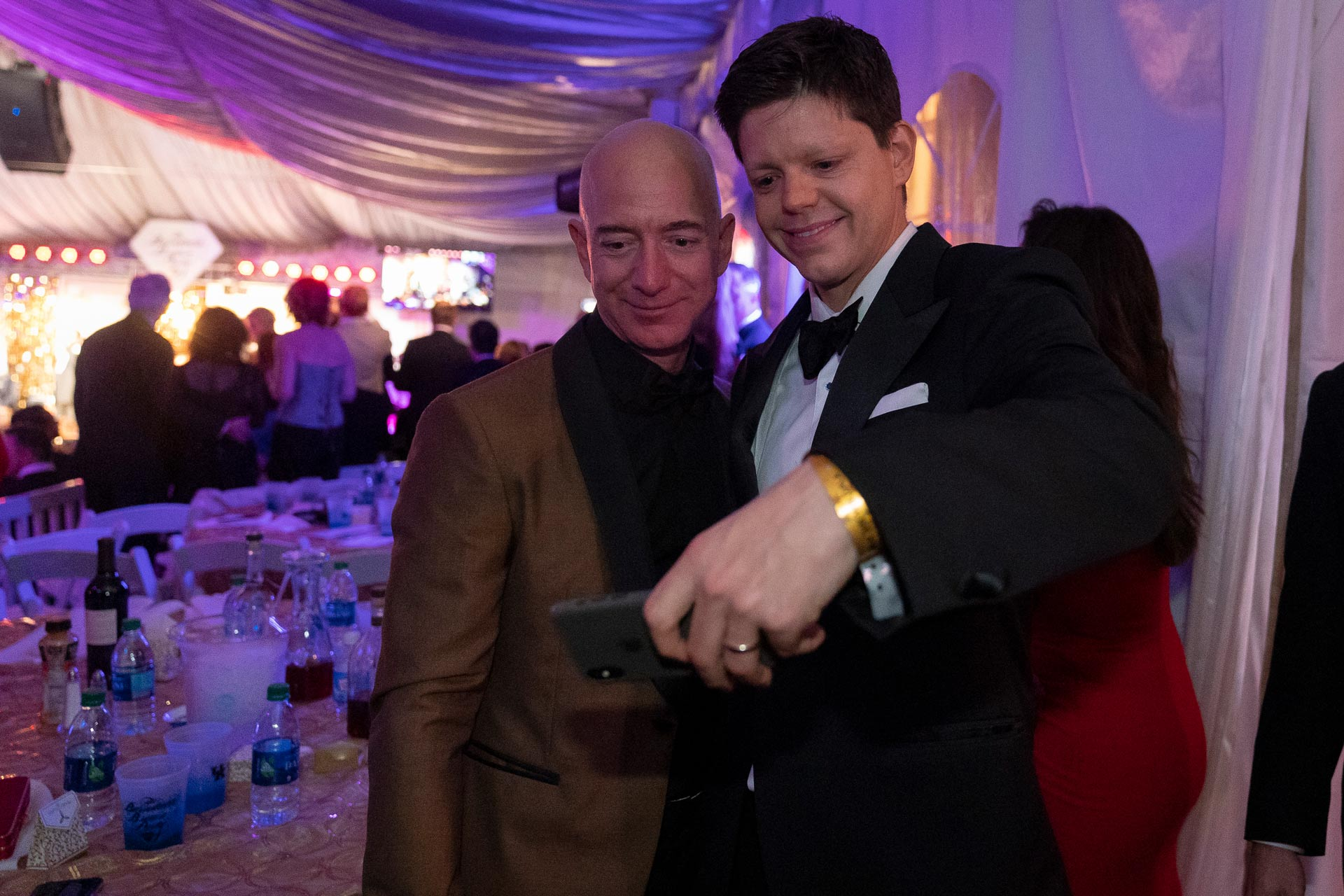 Jeff Bezos, a bald man in a brown and black suit, looks at a phone with Christopher Barnstable-Brown, a tall young man with brown hair, at the Barnstable Brown Gala.